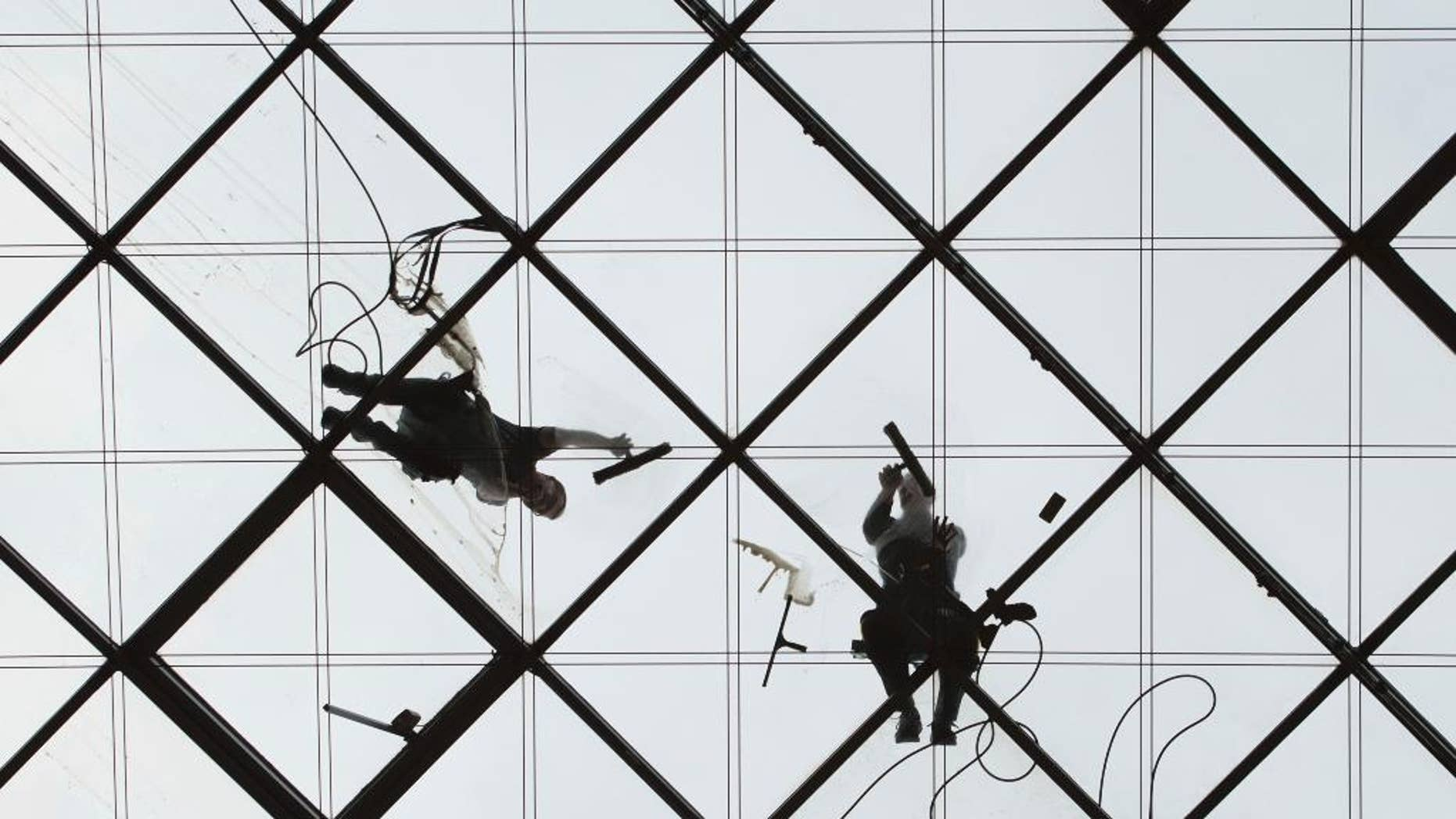 Two workers clean the glass roof of the World Trade Center in Dresden, eastern Germany, Monday, April 3, 2017. (Sebastian Kahnert/dpa via AP)