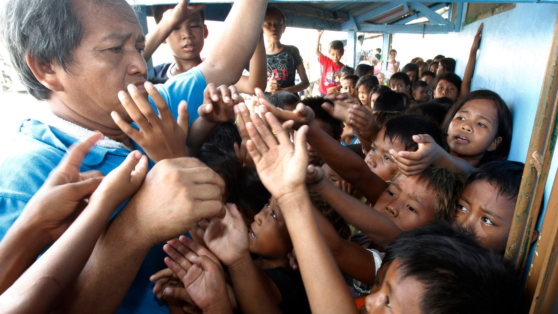Children reach to get a stub for a free meal during a feeding program at a slum area at Baseco, Tondo city, metro Manila May 22, 2013. (REUTERS/Romeo Ranoco)