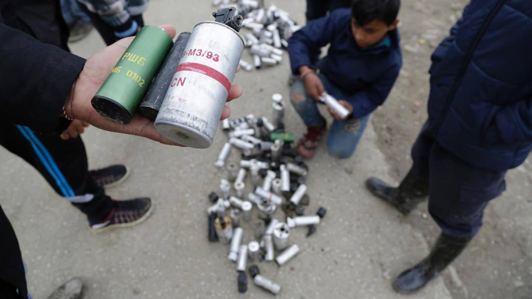 Migrant men shows used tear gas canisters apparently used by Macedonian police during yesterday riots at the fence of a makeshift camp in the northern Greek border point of Idomeni, Greece, Monday, April 11, 2016. More than 12,000 people have been stuck at the Idomeni border point for more than a month hoping that it would reopen. (AP Photo/Amel Emric)