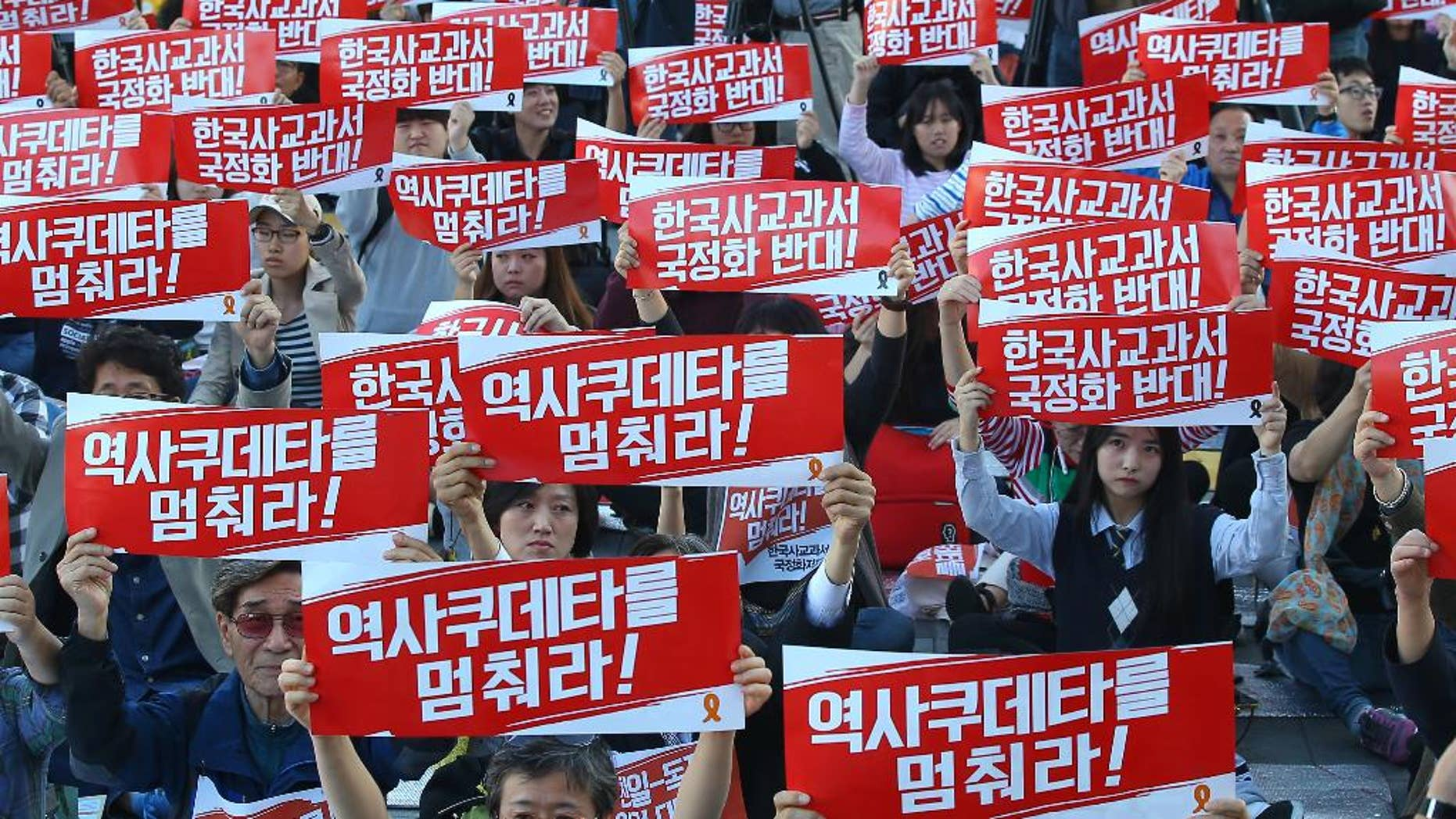 """Protesters shout slogans as they hold banners during a rally to opposite the government plan for the state issued history textbooks in Seoul, South Korea, Saturday, Oct. 17, 2015. Hundreds of South Korean scholars have declared they are boycotting the writing of state-issued history textbooks out of concern that that they will teach distorted views on the country's recent past. The banners read: """"Oppose, the state issued history textbooks."""" (Kim Do-hun/Yonhap via AP) KOREA OUT"""