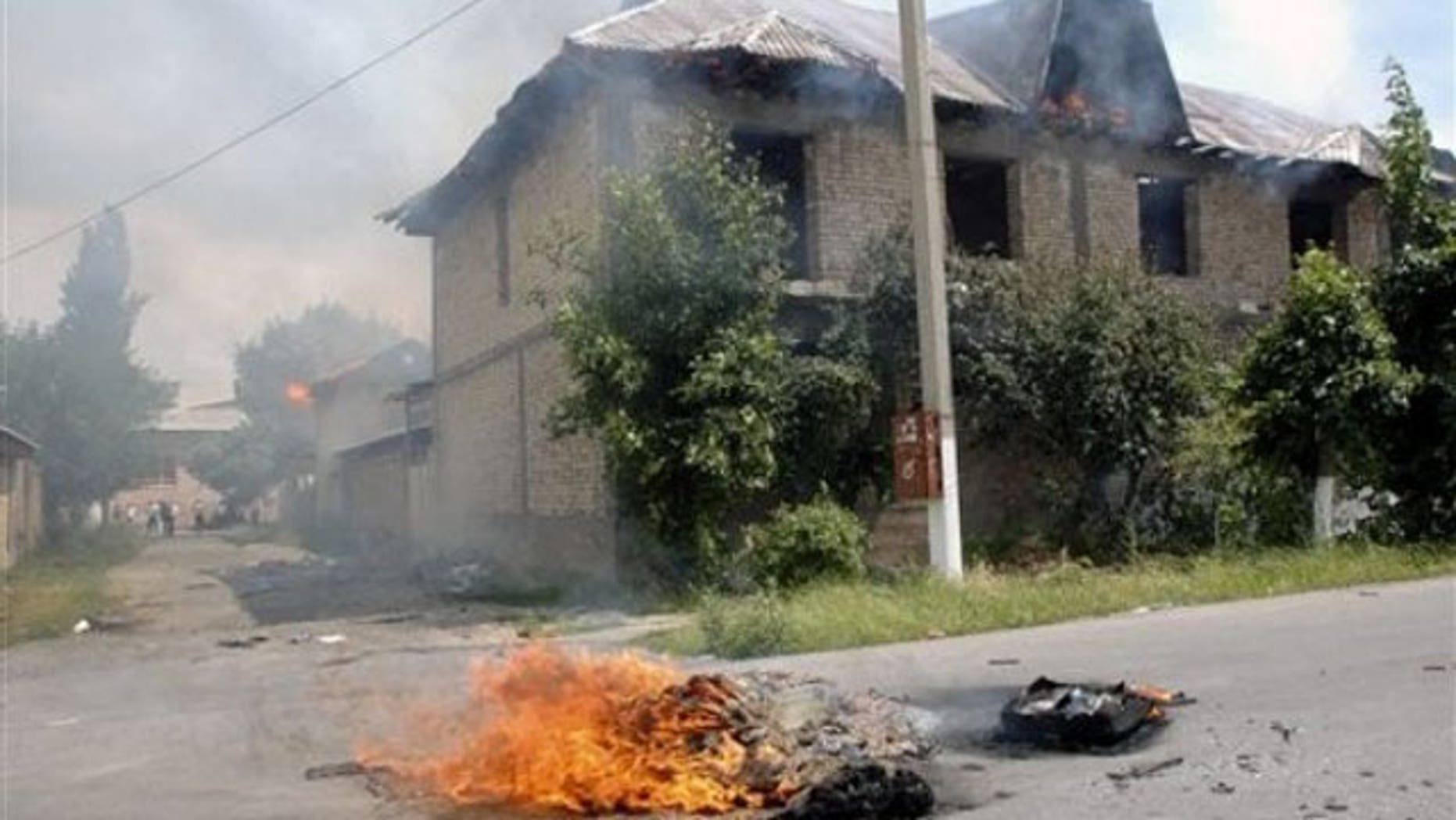 June 13: Ethnic Uzbeks residences burn after being torched by Kyrgyz men, in Jalal-Abad, Kyrgyzstan.