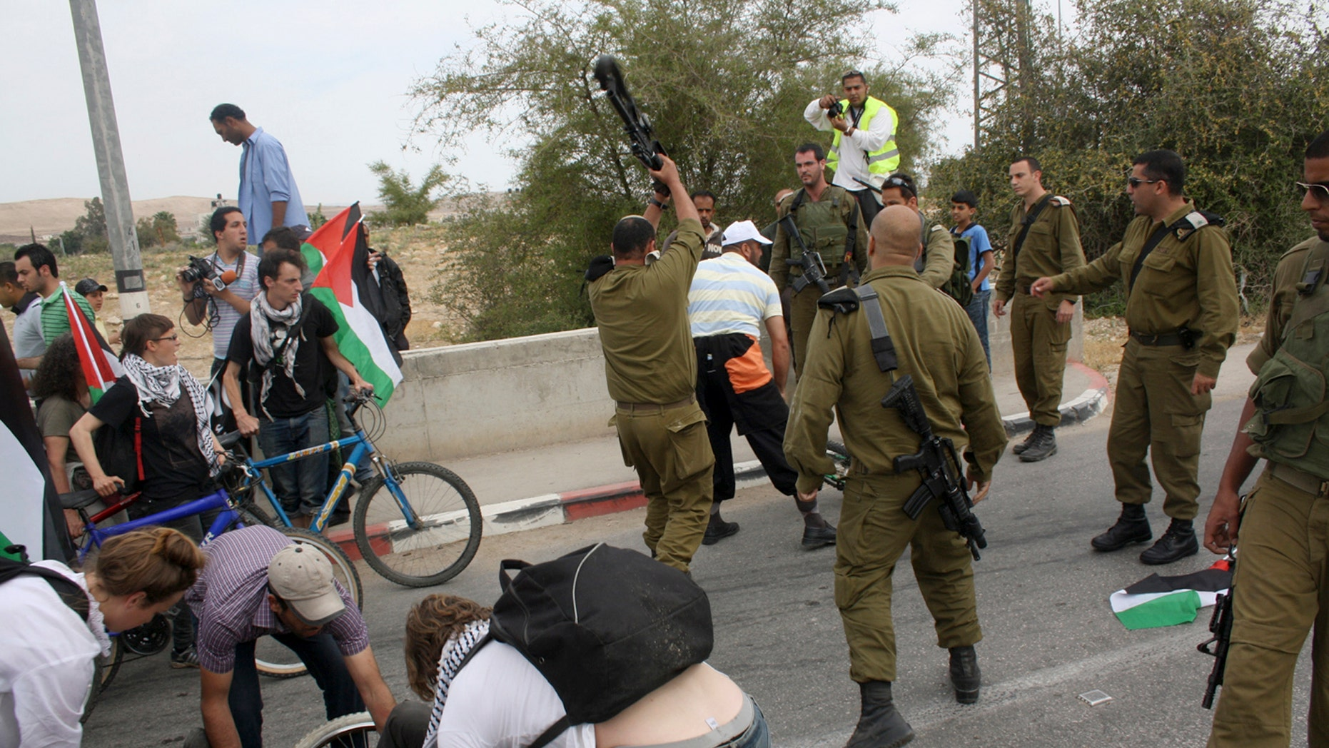 April 14:  Israeli army Lt. Col. Shalom Eisner, seen from back center, hits an unidentified activist with an M-16 rifle in the Jordan Valley.