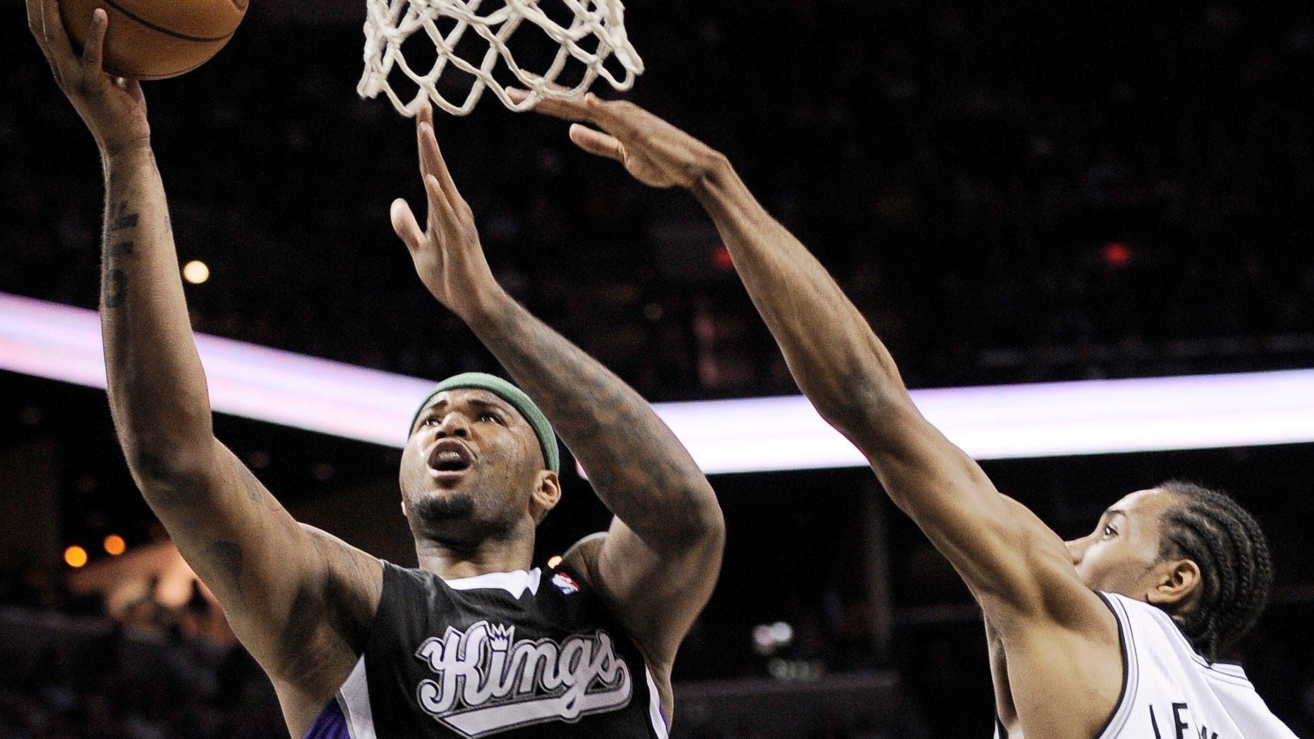 Sacramento Kings' DeMarcus Cousins, left, shoots against San Antonio Spurs' Kawhi Leonard during the second half of an NBA basketball game, Friday, April 12, 2013, in San Antonio. San Antonio won 108-101. (AP Photo/Darren Abate)