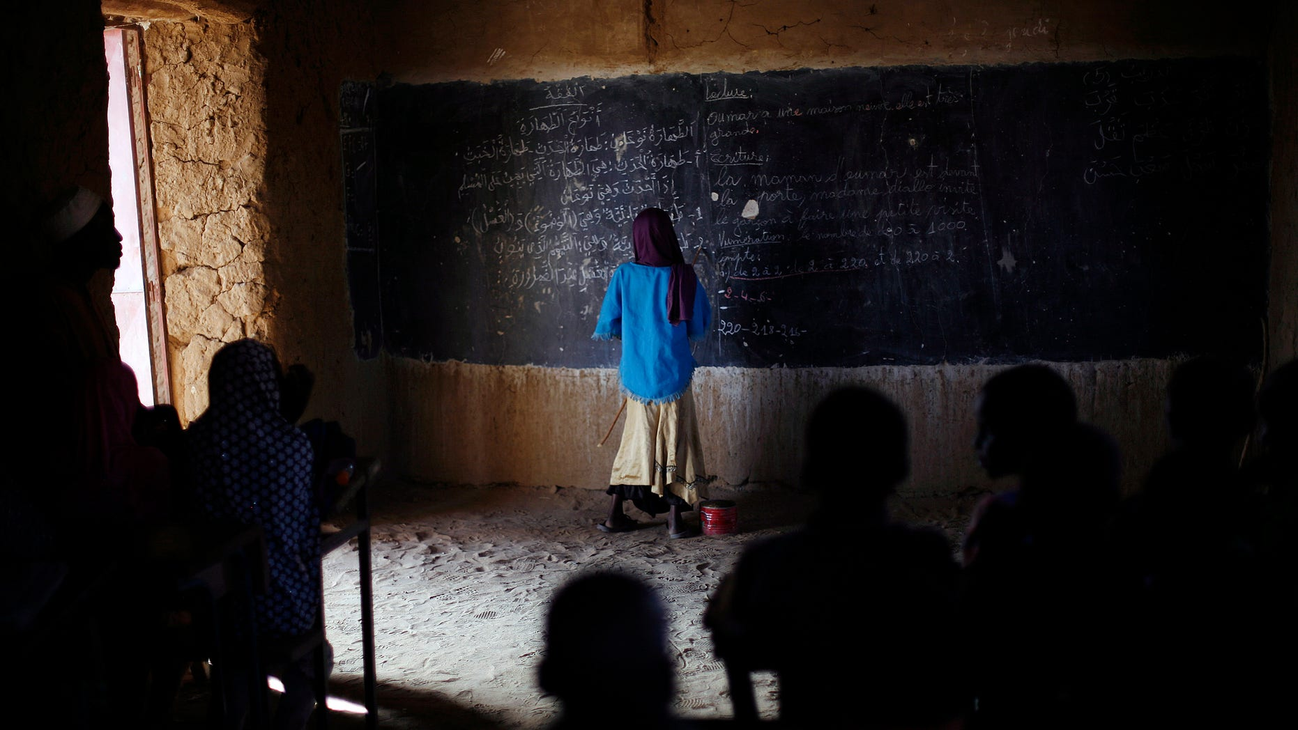 Feb. 18, 2013: A Malian schoolgirl stands at the blackboard as schools reopen in Gao, northern Mali.