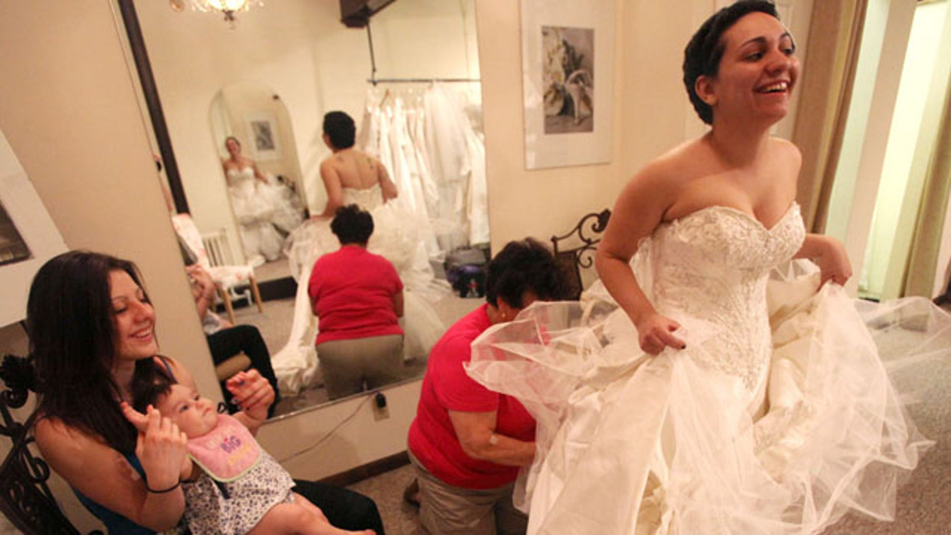 April 8, 2010: Stopping bythe Newburgh dress shop, Bella Coutre, the shop that donated her wedding gown, Jessica Vega is fitted for her wedding gown. Her friend, Kourtney Currier minds Ava at left, while Lorenza Martelli works on the dress.