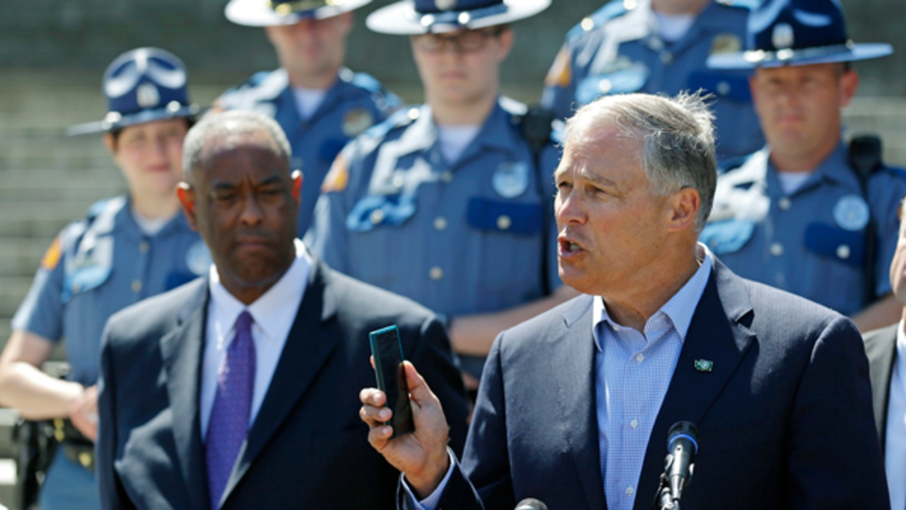 Washington Gov. Jay Inslee, right, holds a cell phone as he speaks during a press event at the Capitol in Olympia, Wash., to raise awareness of Washington state's new law prohibiting the use of nearly all phones and mobile devices while driving.