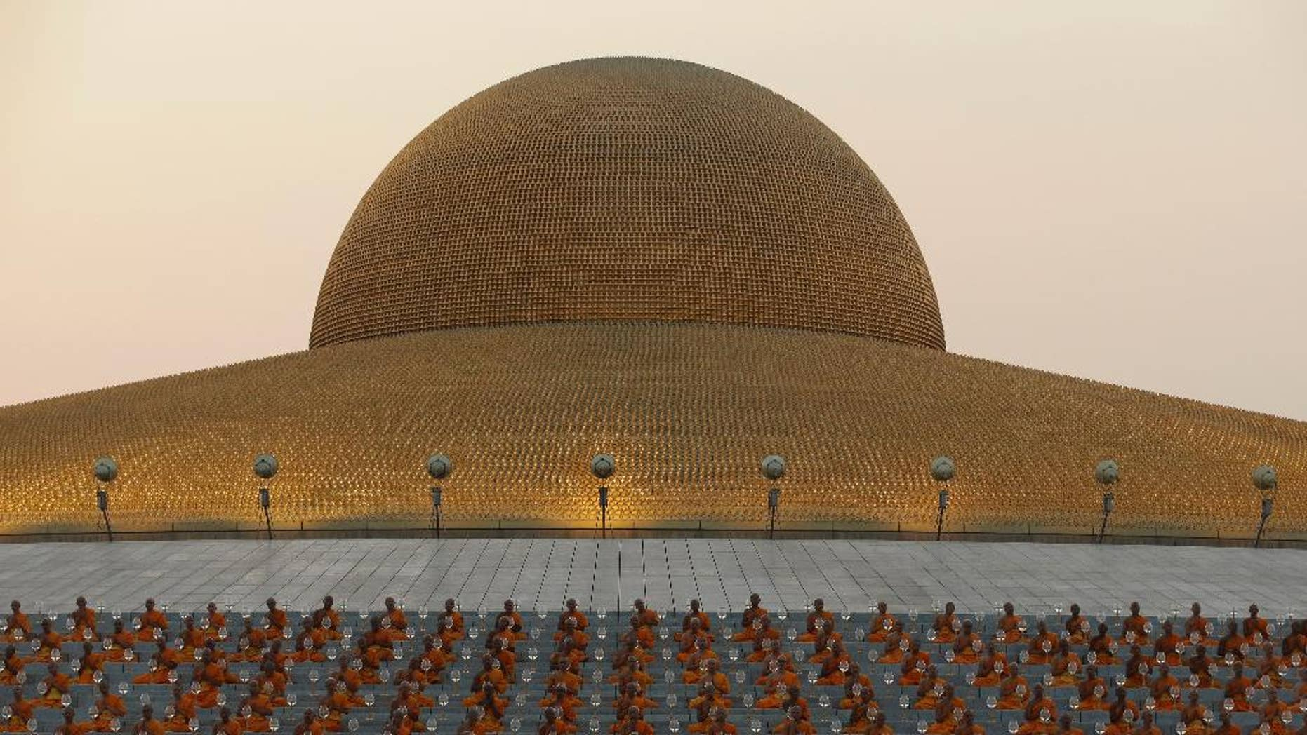 In this Feb. 22, 2016 photo, Thai Buddhist monks pray and gather at Wat Dhammakaya temple to participate in Makha Bucha Day ceremonies in Pathum Thani, Thailand, The Office of the Attorney-General announced Wednesday, Nov. 23, 2016 its decision to bring to court Phra Dhammachayo, the abbot of Wat Dhammakaya, a monastery north of Bangkok. He and four other persons will be charged with conspiracy to launder money, money laundering and receiving stolen property. (AP Photo/Sakchai Lalit)