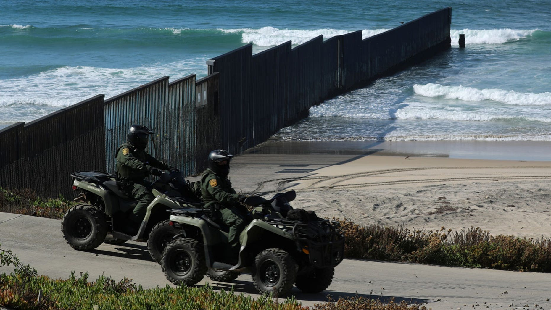 U.S. Customs and Border patrol agents on all-terrain vehicles look over over the Mexico- U.S. border wall where it enters the Pacific Ocean at Border Field State Park in San Diego