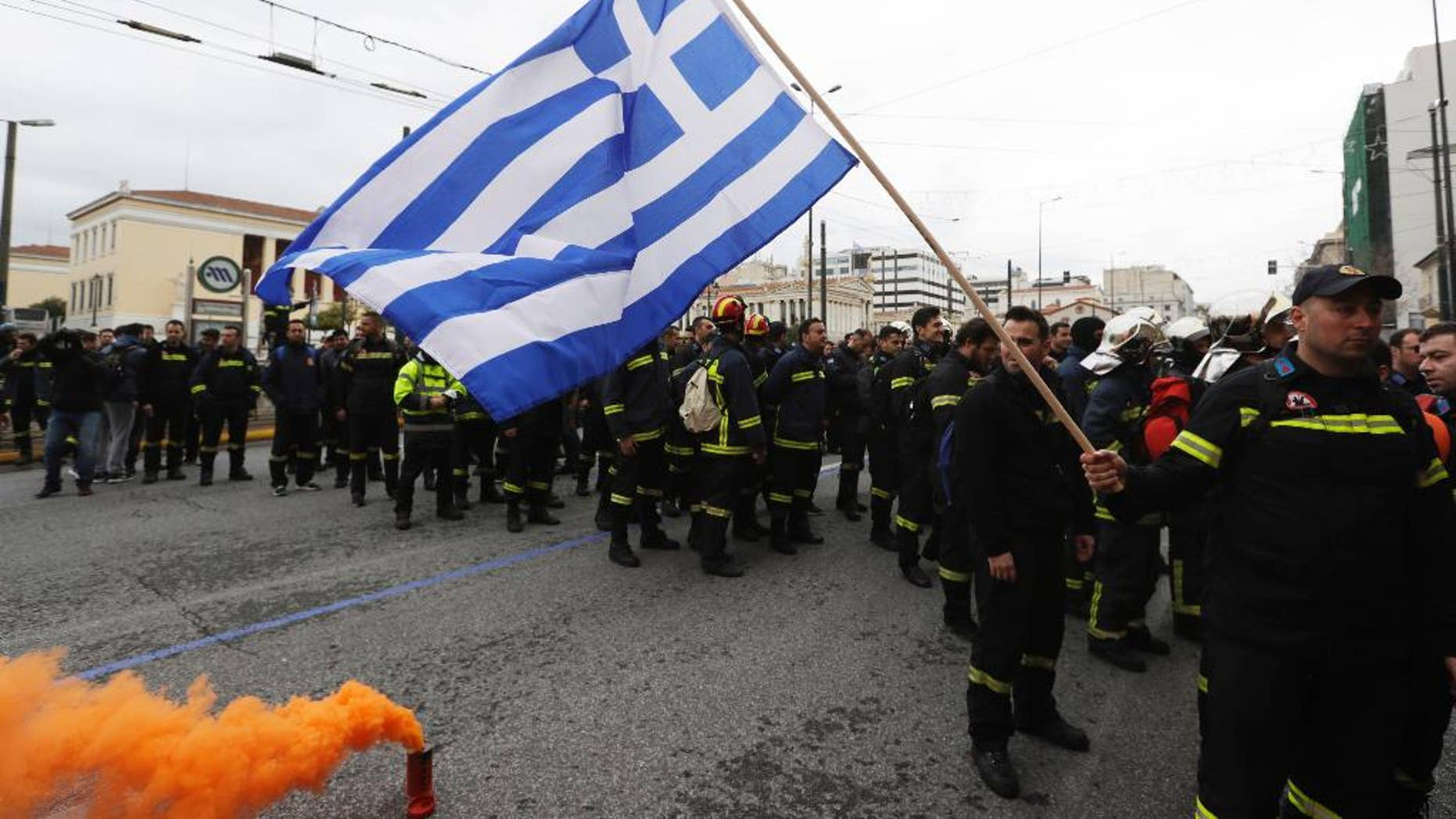 A firefighter holds a Greek flag during a protest in central Athens, on Wednesday, Feb. 8, 2017. Hundreds of firefighters in uniform have taken to the streets of the Greek capital to protest hiring conditions. (AP Photo/Thanassis Stavrakis)