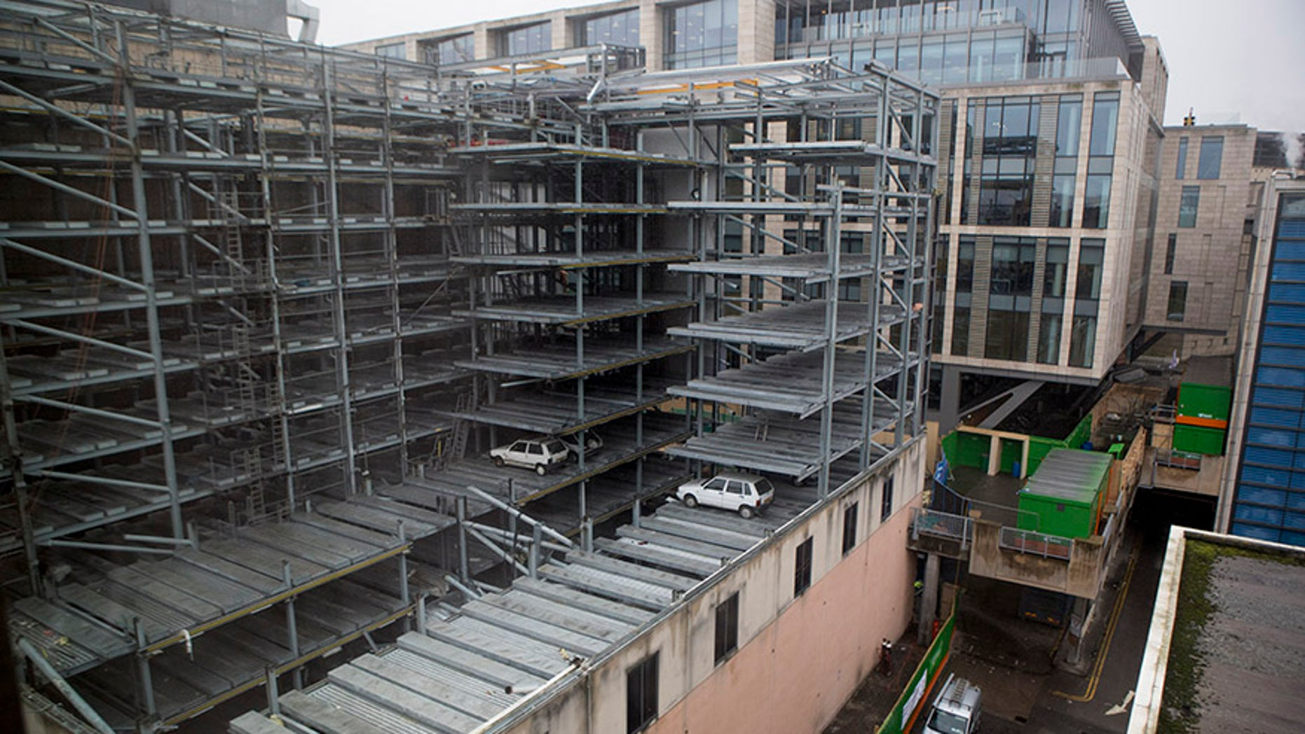 """Cars found trapped in Edinburgh's 'robot car park' 15 years after """"SkyPark"""" closed in 2003. Vehicles imprisoned in a disused robotic car park for more than a decade are set to be preserved by demolition crews after work to redevelop the building got underway. Jan 23 2018. See Centre Press story CPCARS; Eight vehicles stuck in a disused robotic car park for more than a decade will be preserved by demolition crews. The £5 million Autosafe """"SkyPark"""" was hailed as Britain's """"most technologically advanced car park"""" when it opened in Edinburgh in 2001. But the tenure of the car park was short-lived after the company that operated it went into receivership in 2003. It was rumoured at the time that administrators had simply arrived one day to lock the doors, leaving dozens of cars trapped inside. And now, new pictures from a building opposite the site in the centre of Edinburgh show a """"time capsule"""" with vehicles which look to be models from the late 1990s."""
