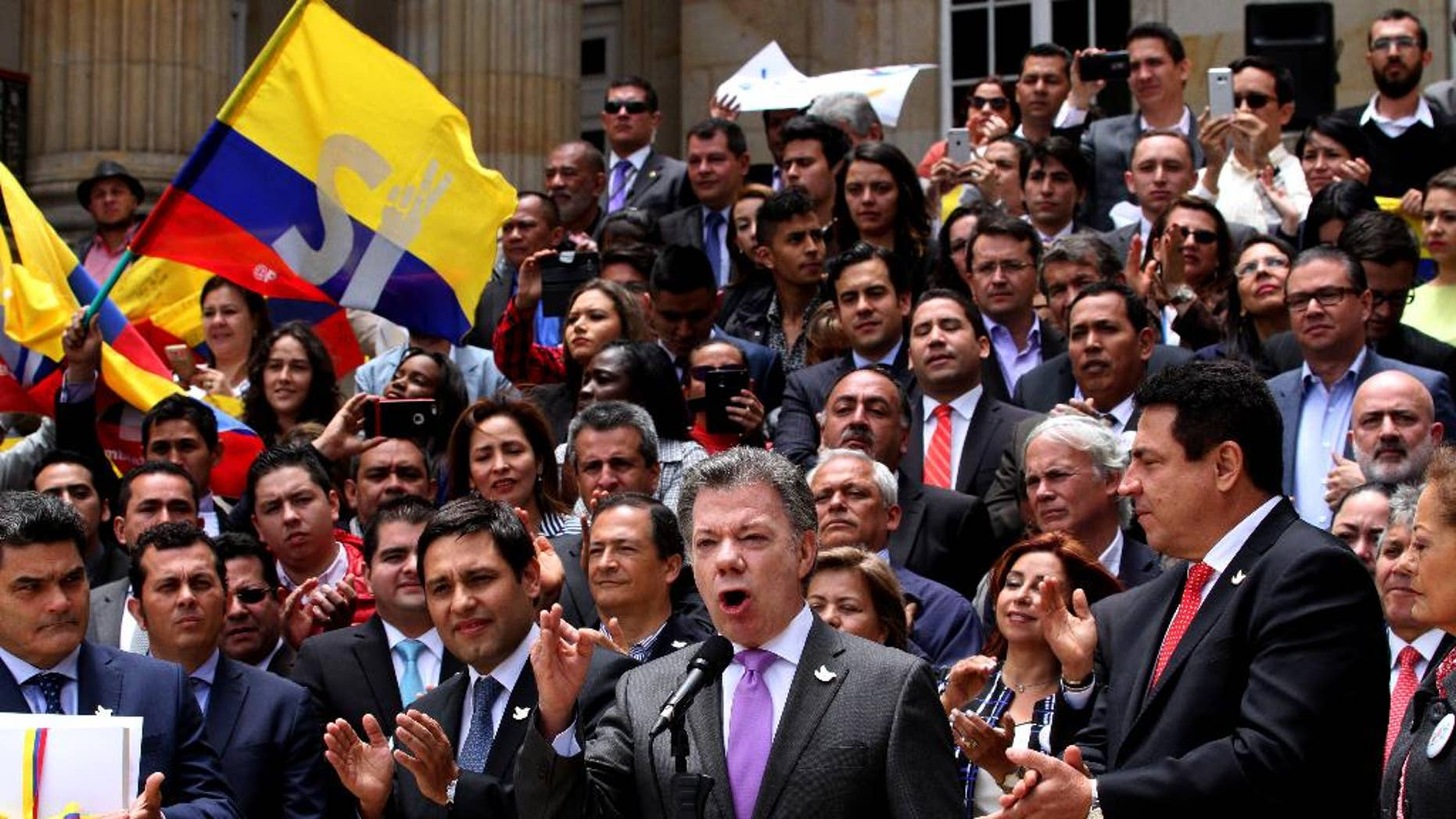 Colombia's President Juan Manuel Santos, front, second from right, speaks after delivering to Congress the peace deal with rebels of the Revolutionary Armed Forces of Colombia, FARC, in Bogota, Colombia, Thursday, Aug. 25, 2016. Santos is moving fast to hold a national referendum on a peace deal meant to end a half-century conflict with leftist rebels, delivering the final text of the deal on Thursday to Congress and declaring a definitive ceasefire against the guerrillas.(AP Photo/Felipe Caicedo)