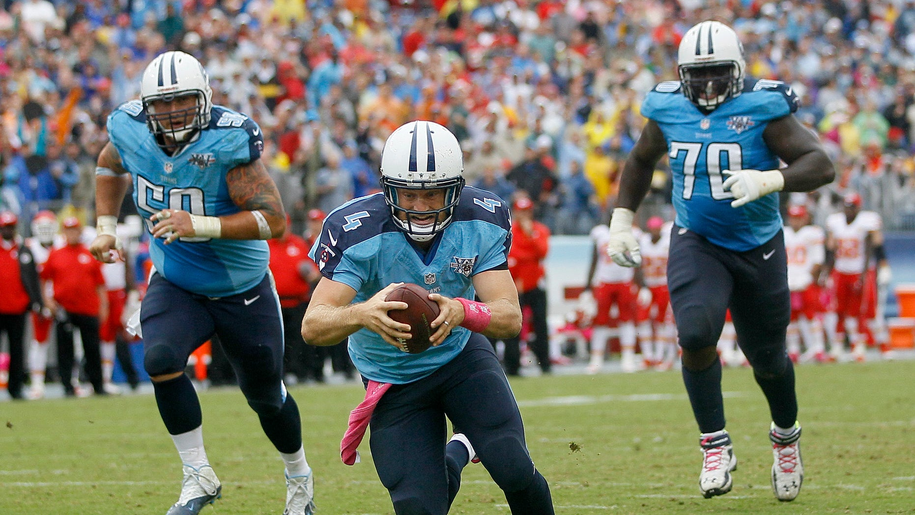 Tennessee Titans quarterback Ryan Fitzpatrick (4) dives into the end zone to score a touchdown on a 9-yard run against the Kansas City Chiefs in the fourth quarter of an NFL football game on Sunday, Oct. 6, 2013, in Nashville, Tenn. Titans linemen Rob Turner (59) and Chance Warmack (70) follow Fitzpatrick. (AP Photo/Wade Payne)