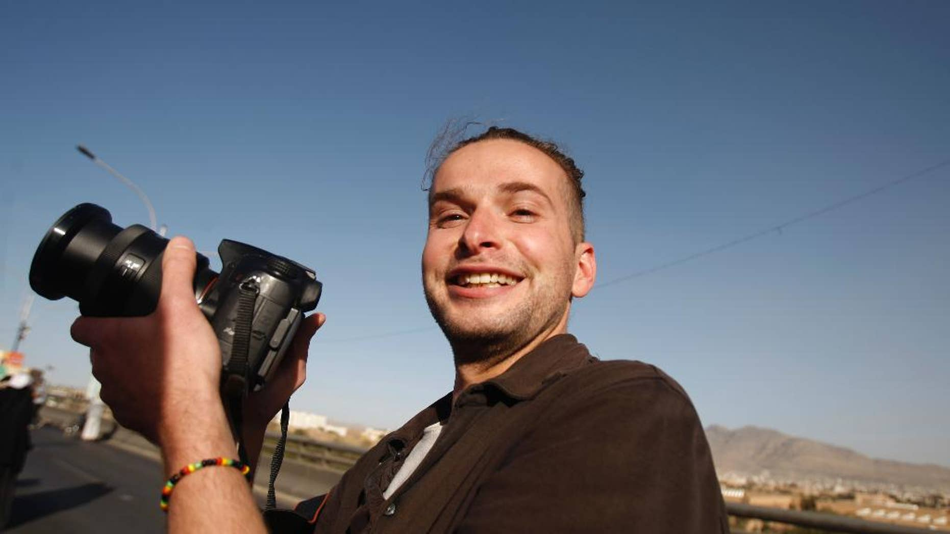 FILE - In this Monday, Feb. 11, 2013 file photo, Luke Somers, 33, an American photojournalist who was kidnapped over a year ago by al-Qaida, poses for a picture during a parade marking the second anniversary of the revolution in Sanaa, Yemen. Somers has been killed in a failed rescue attempt, his sister said Saturday, Dec. 6, 2014. Lucy Somers told The Associated Press that she and her father learned of her 33-year-old brother Luke Somers' death from FBI agents at 0500 GMT (12 a.m. EST) Saturday. (AP Photo/Hani Mohammed, File)