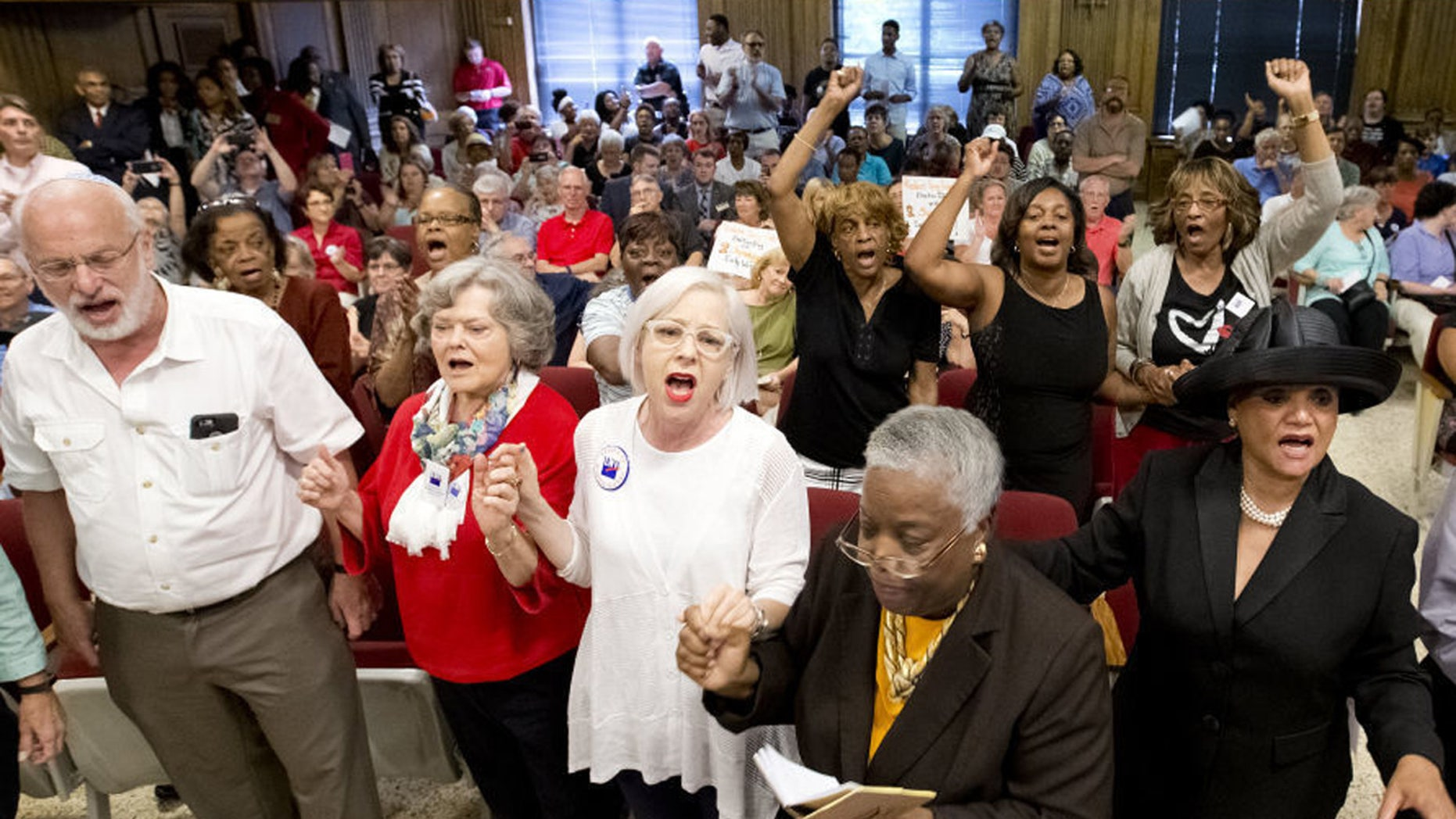 In this Aug. 9, 2016 file photo, people rise and begin singing during the Guilford County Board of Elections meeting at the Old Guilford County Courthouse in Greensboro, N.C.