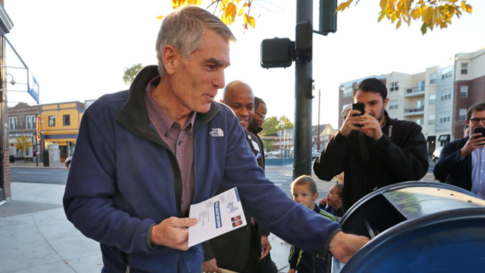 FILE: Oct. 20, 2014: Sen. Mark Udall, D-Colo., mails his ballot, in the Five Points area of Denver. Colo.