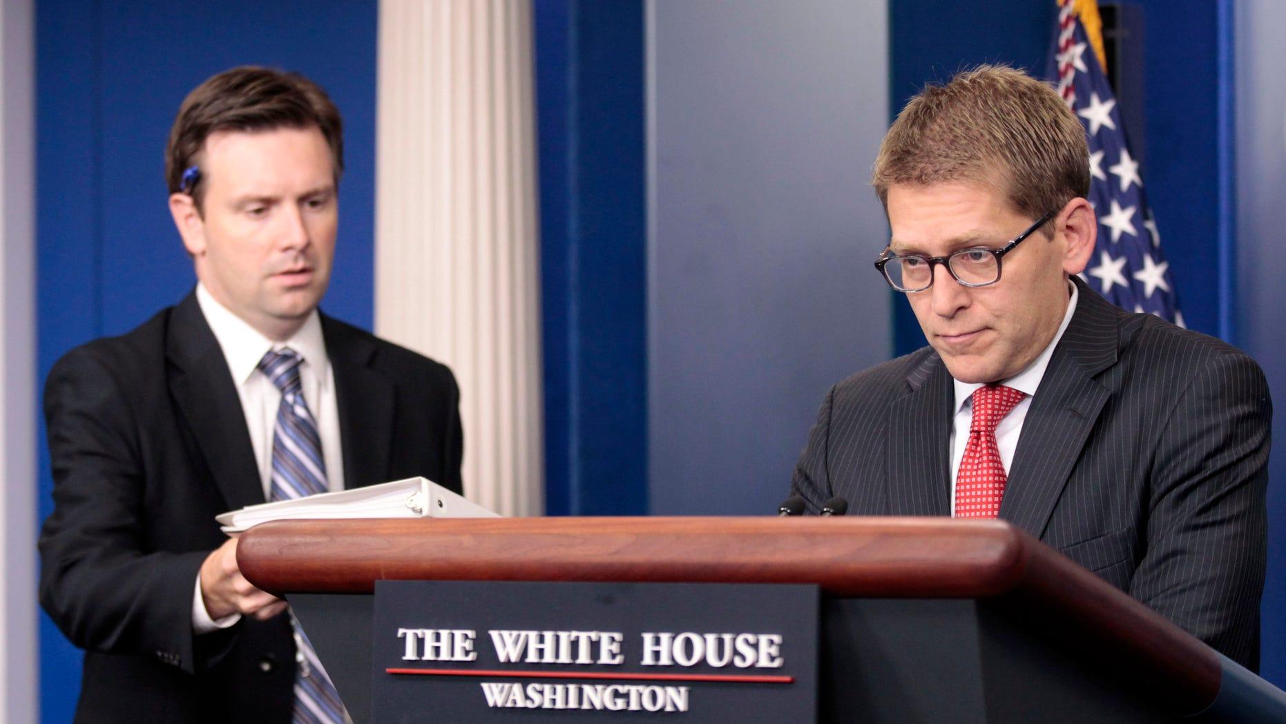 Wednesday: Principal Deputy Press Secretary Josh Earnest, left, hands off the briefing book to White House Press Secretary Jay Carney during the daily news briefing at the White House.