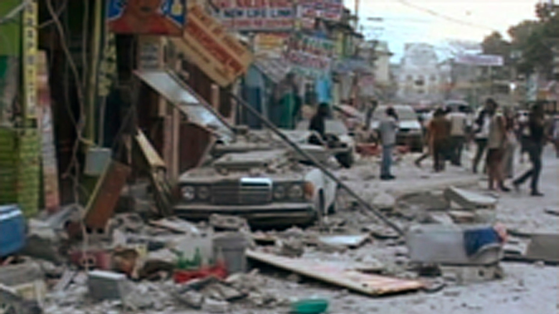 A car damaged after an earthquake struck is seen in Port-au-Prince in this January 12, 2010 video grab. A major earthquake hit impoverished Haiti on Tuesday, toppling buildings in the capital Port-au-Prince, burying residents in rubble and causing many deaths and injuries, witnesses in the city said.