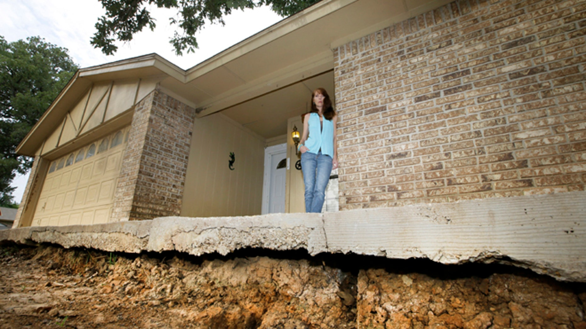 June 21, 2014: Barbara Brown poses for a photo on the front step of her home that now sits about one foot off the surface of her lawn.