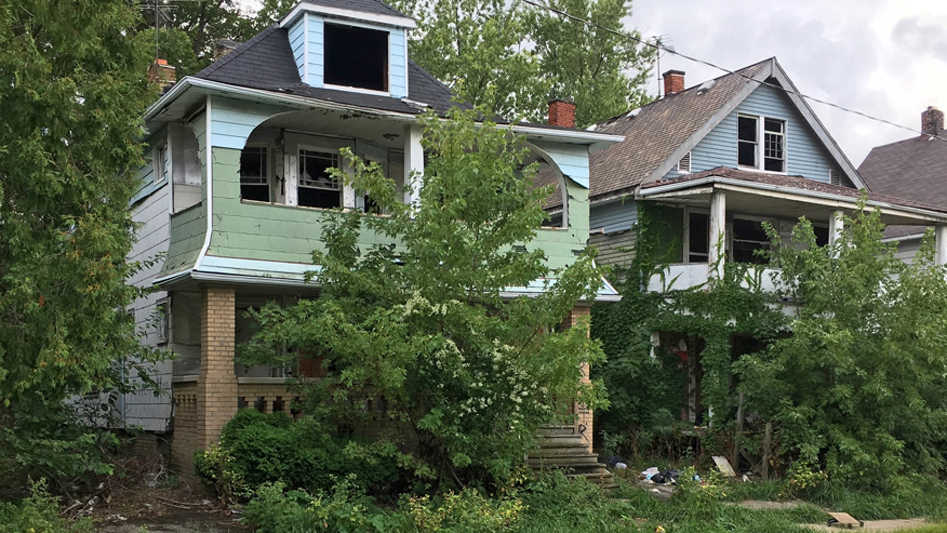 This Aug. 31, 2016, photo shows houses with missing windows and overgrown lawns along a street marred by cracks and potholes in East Cleveland, Ohio. Cleveland and East Cleveland, two of the country's poorest cities, are debating whether to merge, with both cities saying the state of Ohio needs to provide millions to begin fixing East Cleveland's infrastructure and finances.