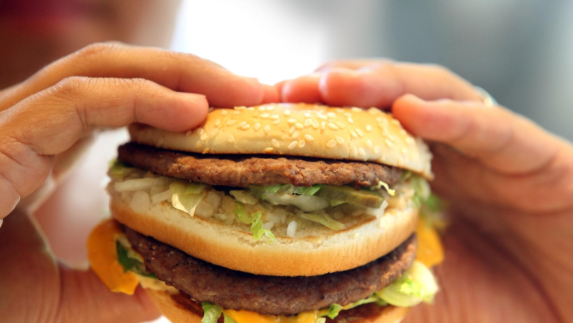 man's hands, holding onto a burger