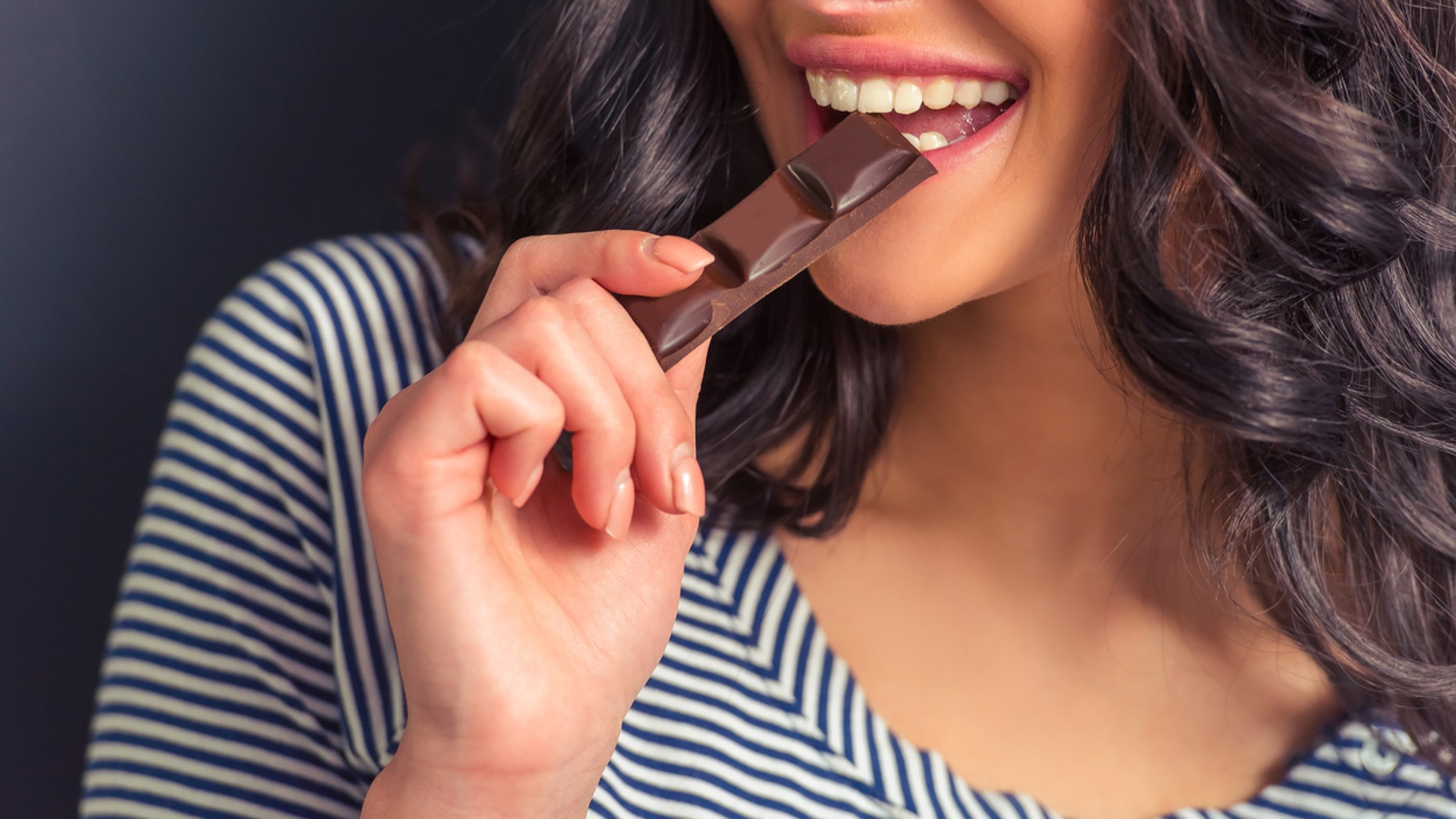 Cropped image of attractive girl eating chocolate and smiling, against dark background