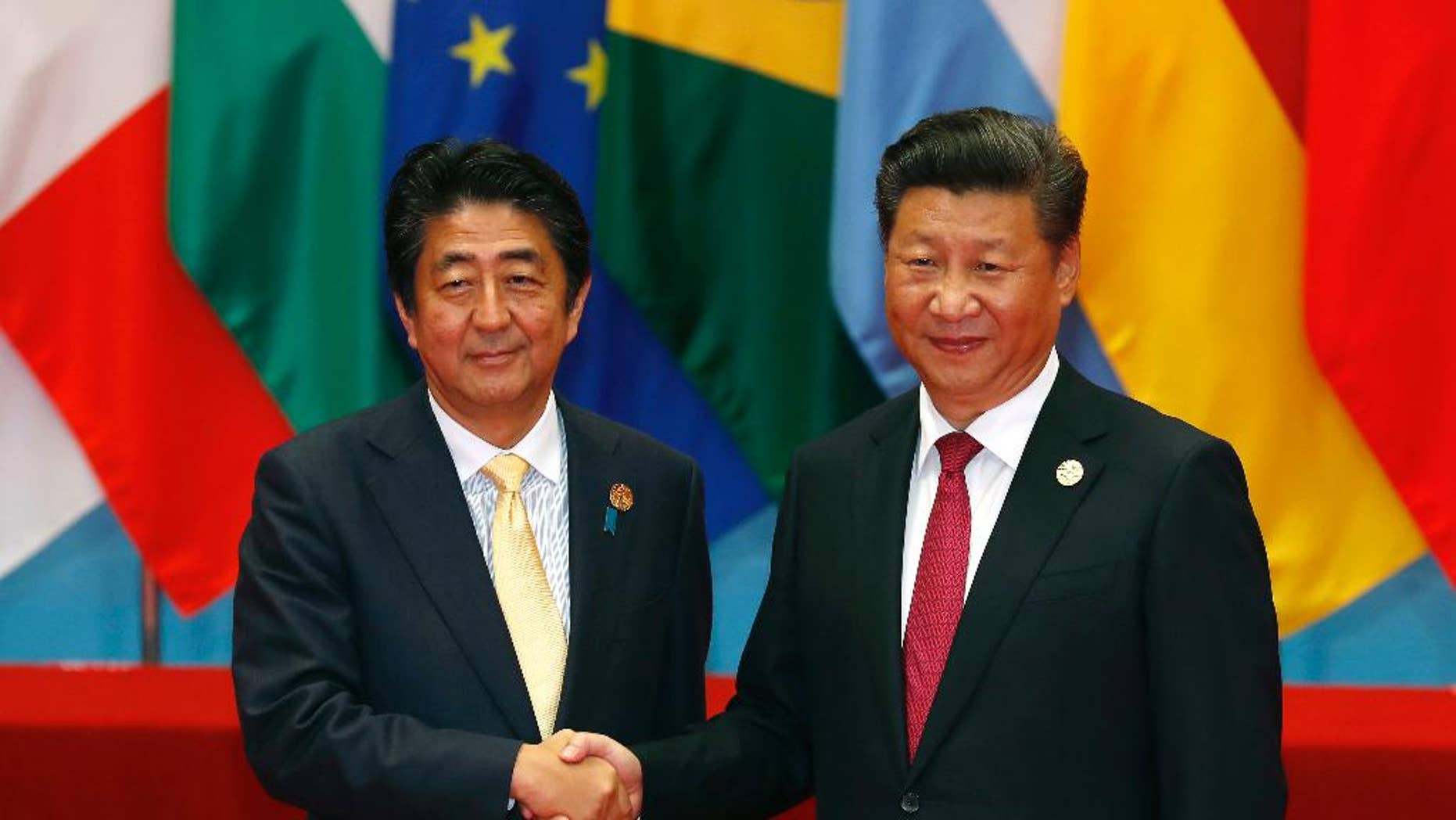 "FILE- In this Sunday, Sept. 4, 2016, file photo, Japan's Prime Minister Shinzo Abe, left, poses with China's President Xi Jinping for a photo before a group photo session for the G20 Summit in Hangzhou in eastern China's Zhejiang province. Four years after they went into a nosedive, tense relations between China and Japan may finally be headed for a sustained return to some semblance of normalcy. Those hopes rest largely on a statement by Chinese President Xi Jinping at a meeting Monday with Japanese Prime Minister Shinzo Abe that it was time to ""put aside disruptions"" and bring ties ""back on the normal track."" (AP Photo/Ng Han Guan, File)"