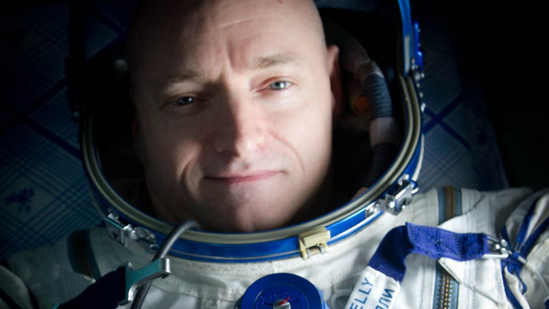 """Expedition 26 Commander Scott Kelly wears a blue wrist band that has a peace symbol, a heart and the word """"Gabby"""" to show his love of his sister-in-law U.S. Rep. Gabrielle Giffords as he rests onboard a Russian Search and Rescue helicopter shortly after he and fellow crew members Oleg Skripochka and Alexander Kaleri landed in their Soyuz TMA-01M capsule near the town of Arkalyk, Kazakhstan on Wednesday, March 16, 2011."""