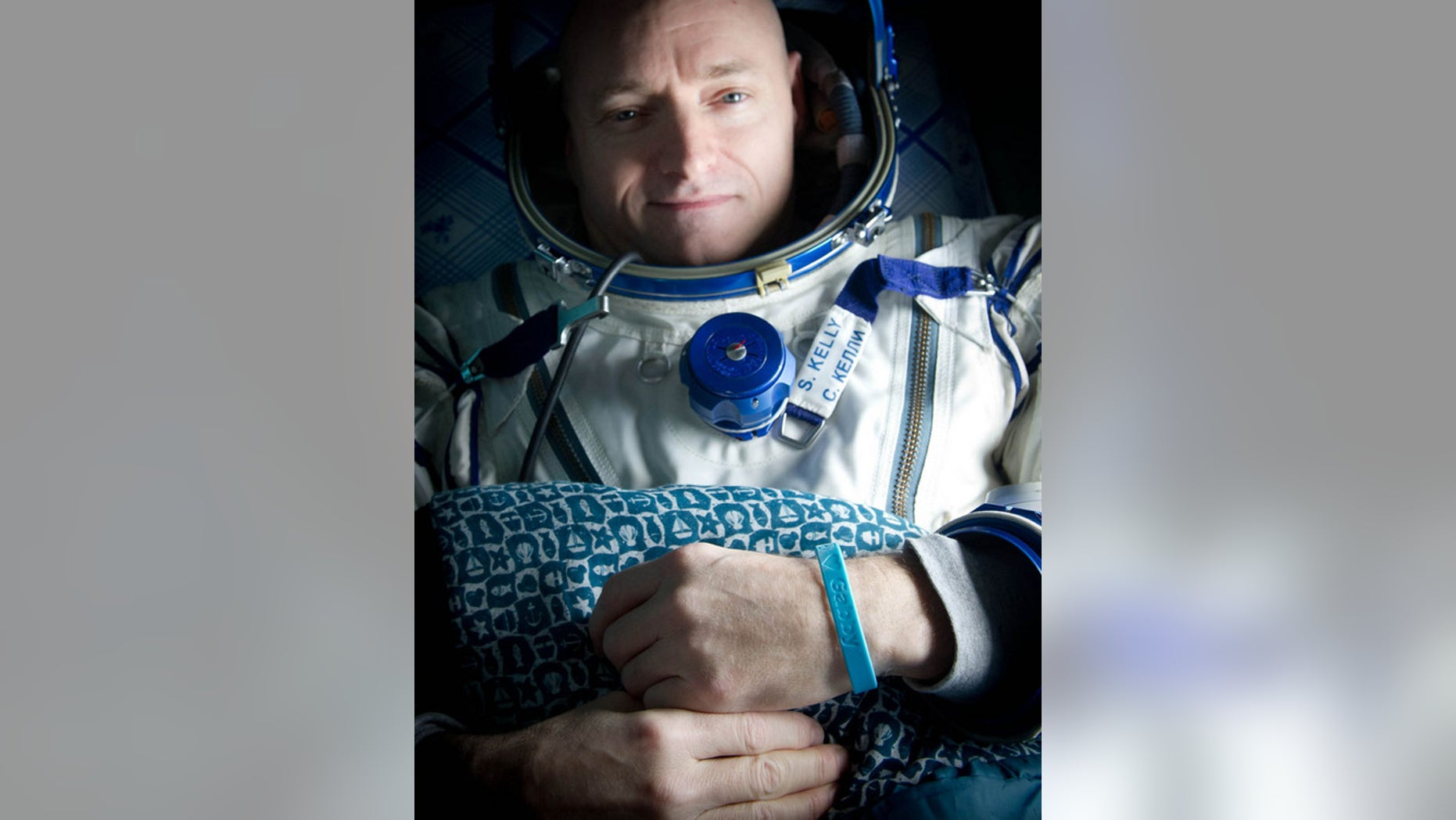 "Expedition 26 Commander Scott Kelly wears a blue wrist band that has a peace symbol, a heart and the word ""Gabby"" to show his love of his sister-in-law U.S. Rep. Gabrielle Giffords as he rests onboard a Russian Search and Rescue helicopter shortly after he and fellow crew members Oleg Skripochka and Alexander Kaleri landed in their Soyuz TMA-01M capsule near the town of Arkalyk, Kazakhstan on Wednesday, March 16, 2011."