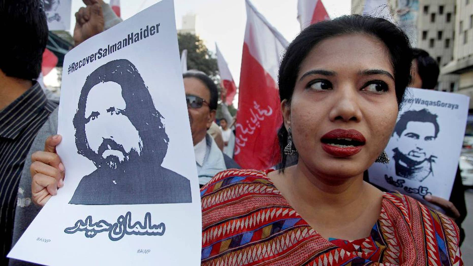 FILE - In this Tuesday, Jan. 10, 2017 file photo, a woman joins other demonstrators to condemn missing human rights activists, in Karachi, Pakistan. Pakistan banned Amir Liaqat, a TV host, over incitement and registered a criminal case against him Thursday, Jan. 26, 2017, after he called for five missing human rights activists and other liberal Pakistanis to be killed for blasphemy and sedition, officials said. The state media regulator said that Liaqat, a self-styled religious scholar, could no longer appear on the pro-military BOL TV, where he hosted a daily program, or any other local broadcast. (AP Photo/Fareed Khan, File)