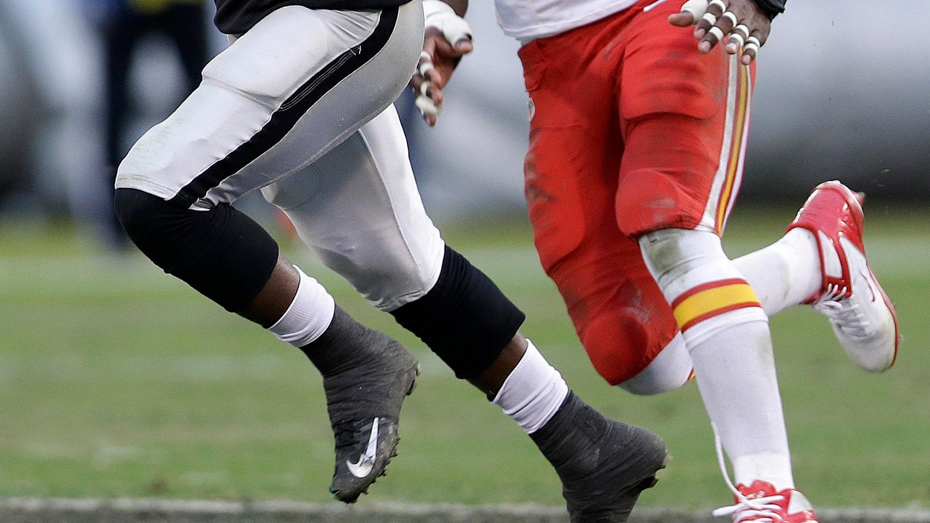 Oakland Raiders running back Mike Goodson (25) runs past Kansas City Chiefs outside linebacker Justin Houston (50) during the third quarter of an NFL football game in Oakland, Calif., Sunday, Dec. 16, 2012. (AP Photo/Marcio Jose Sanchez)