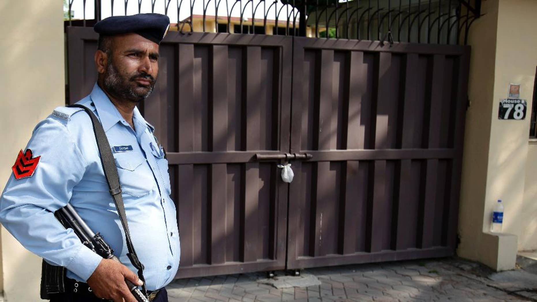 """A Pakistani police officer stands guard outside a sealed office of international aid group Save the Children , in Islamabad, Pakistan, Sunday, June 14, 2015. Pakistan's Interior Ministry has halted an order it made closing the office of Save the Children in Islamabad, an official said Sunday. On Thursday, Pakistan shuttered the group's main office in the capital for allegedly """"violating its charter.""""  (AP Photo/Anjum Naveed)"""