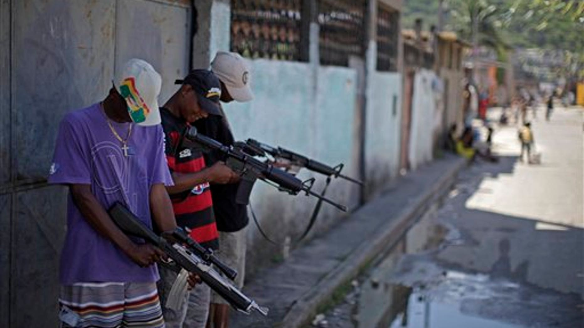 Nov. 27: Alleged drug traffickers who did not want to identify themselves, hold their weapons while posing for a photo at a slum in western Rio de Janeiro, Brazil.