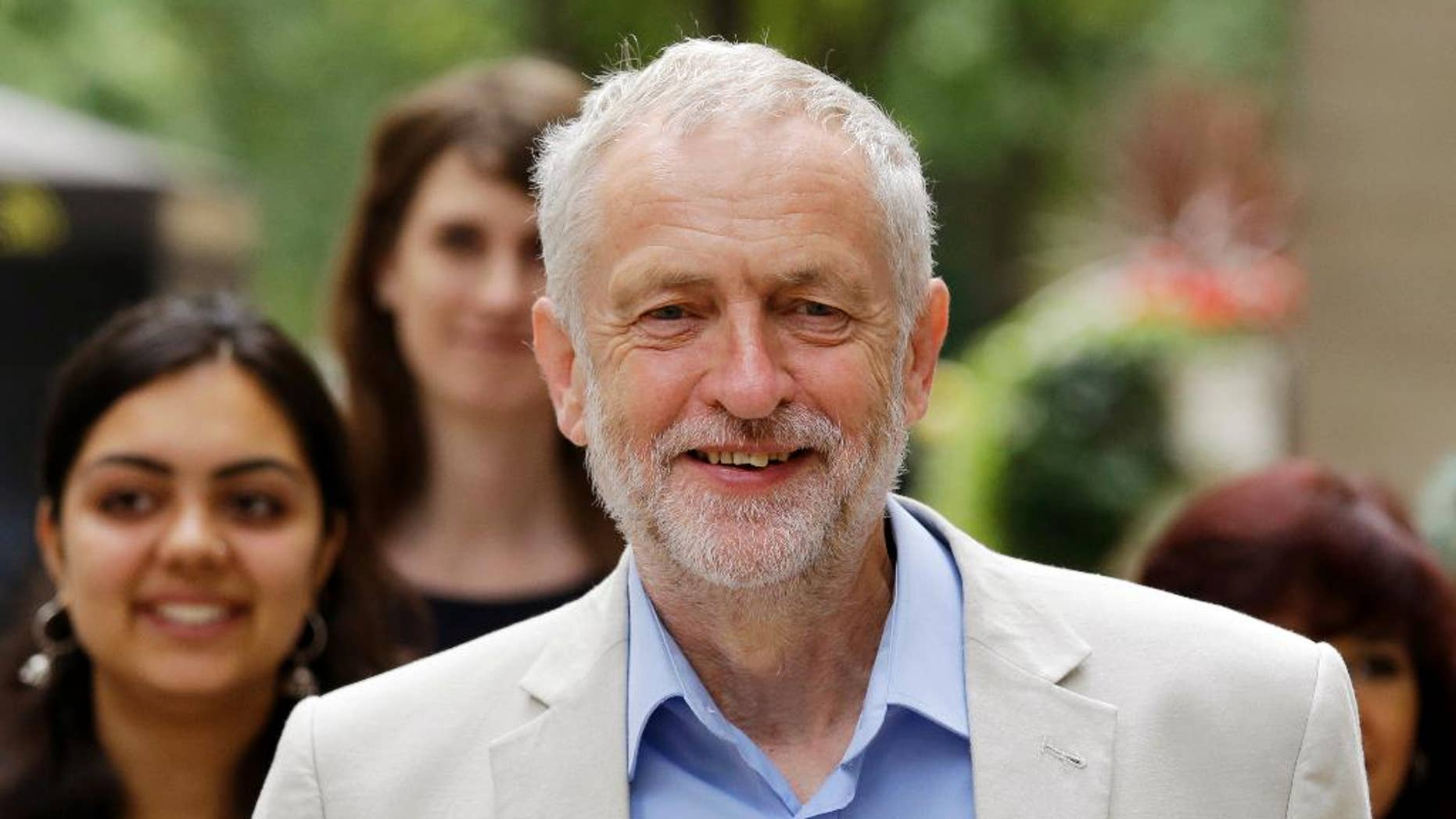 FILE - In this Thursday, July 21, 2016 file photo, British Labour Party leader Jeremy Corbyn walks with supporters as he arrives for a press conference to launch his bid to retain the leadership of the party in London. Britain's High Court on Thurday, July 28 has struck down an attempt to remove the lead of the country's divided Labour opposition from a contest for the party leadership. Labour lawmakers are trying to unseat leader Jeremy Corbyn, a 67-year-old left-winger considered unelectable by the party's more centrist members. (AP Photo/Matt Dunham, file)