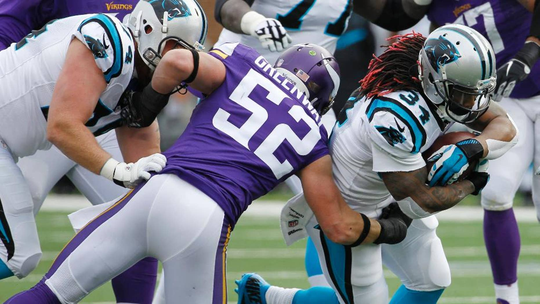 Carolina Panthers running back DeAngelo Williams (34) tries to break a tackle by Minnesota Vikings outside linebacker Chad Greenway (52) during the first half of an NFL football game, Sunday, Nov. 30, 2014, in Minneapolis. (AP Photo/Ann Heisenfelt)