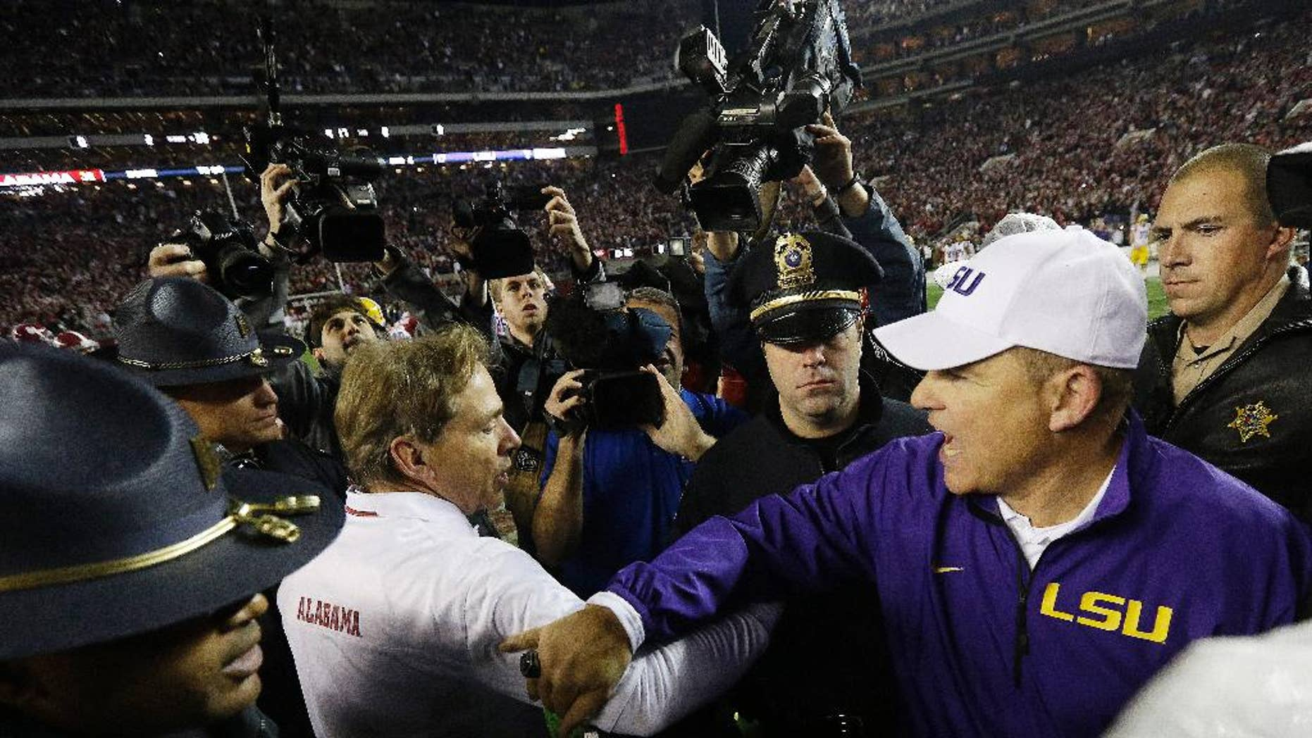 FILE - In this Nov. 9, 2013, file photo, Alabama head coach Nick Saban speaks with LSU head coach Les Miles after an NCAA college football game in Tuscaloosa, Ala.  (AP Photo/Dave Martin, File)