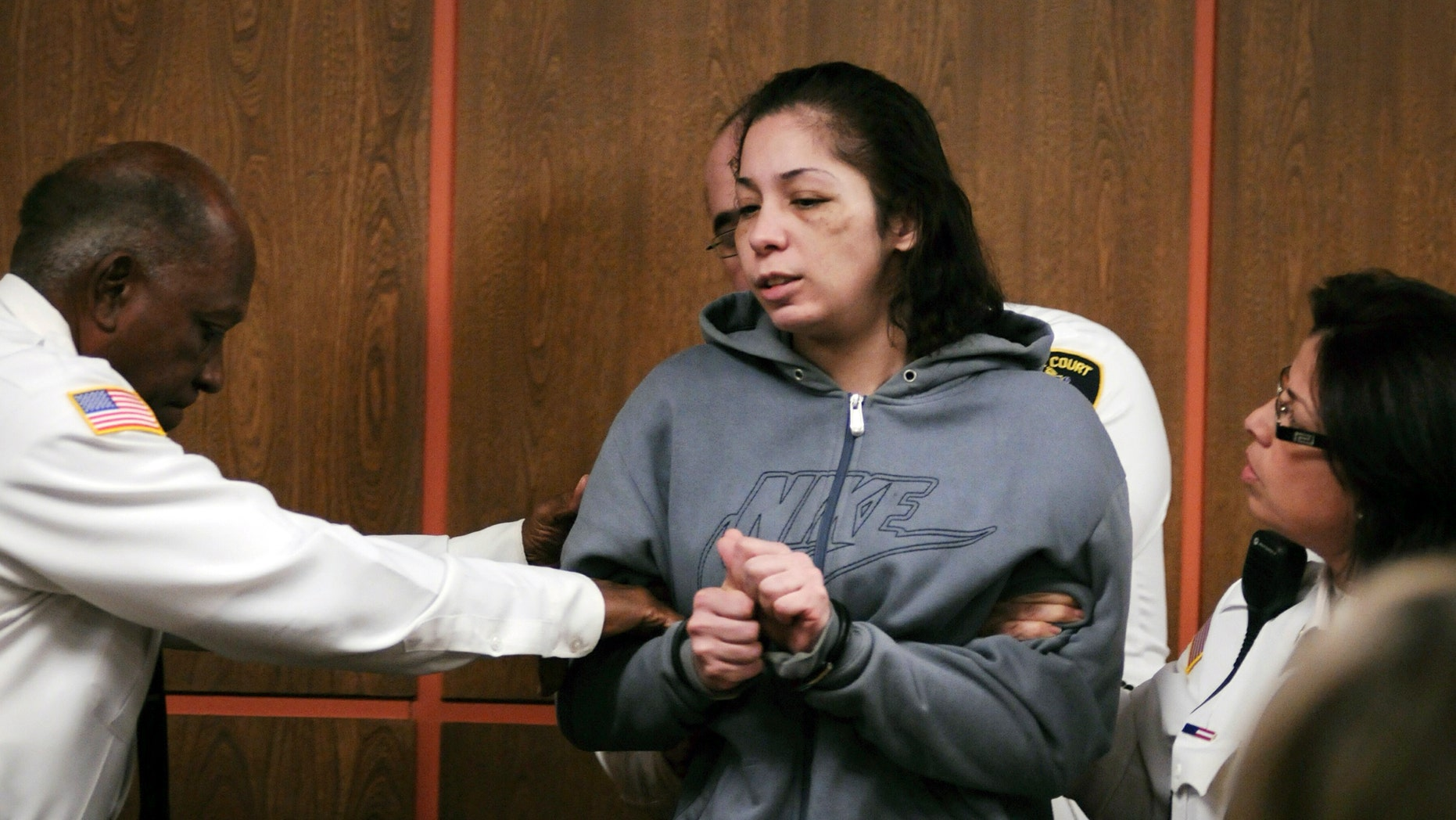 Elsa Oliver is escorted into the courtroom for her arraignment in Fitchburg District Court Tuesday, Dec. 17, 2013, in Fitchburg, Mass., on on charges of reckless endangerment of a child and accessory after the fact of assault, in regards to her missing 5-year-old son, Jeremiah Oliver. (AP Photo/Worcester Telegram & Gazette, Rick Cinclair, Pool)