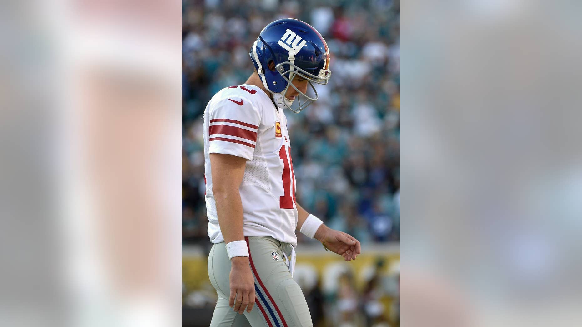 New York Giants quarterback Eli Manning (10) walks off the field after fumbling on their final possession of the second half of an NFL football game against the Jacksonville Jaguars in Jacksonville, Fla., Sunday, Nov. 30, 2014. The Jaguars won 25-24.(AP Photo/Phelan M. Ebenhack)