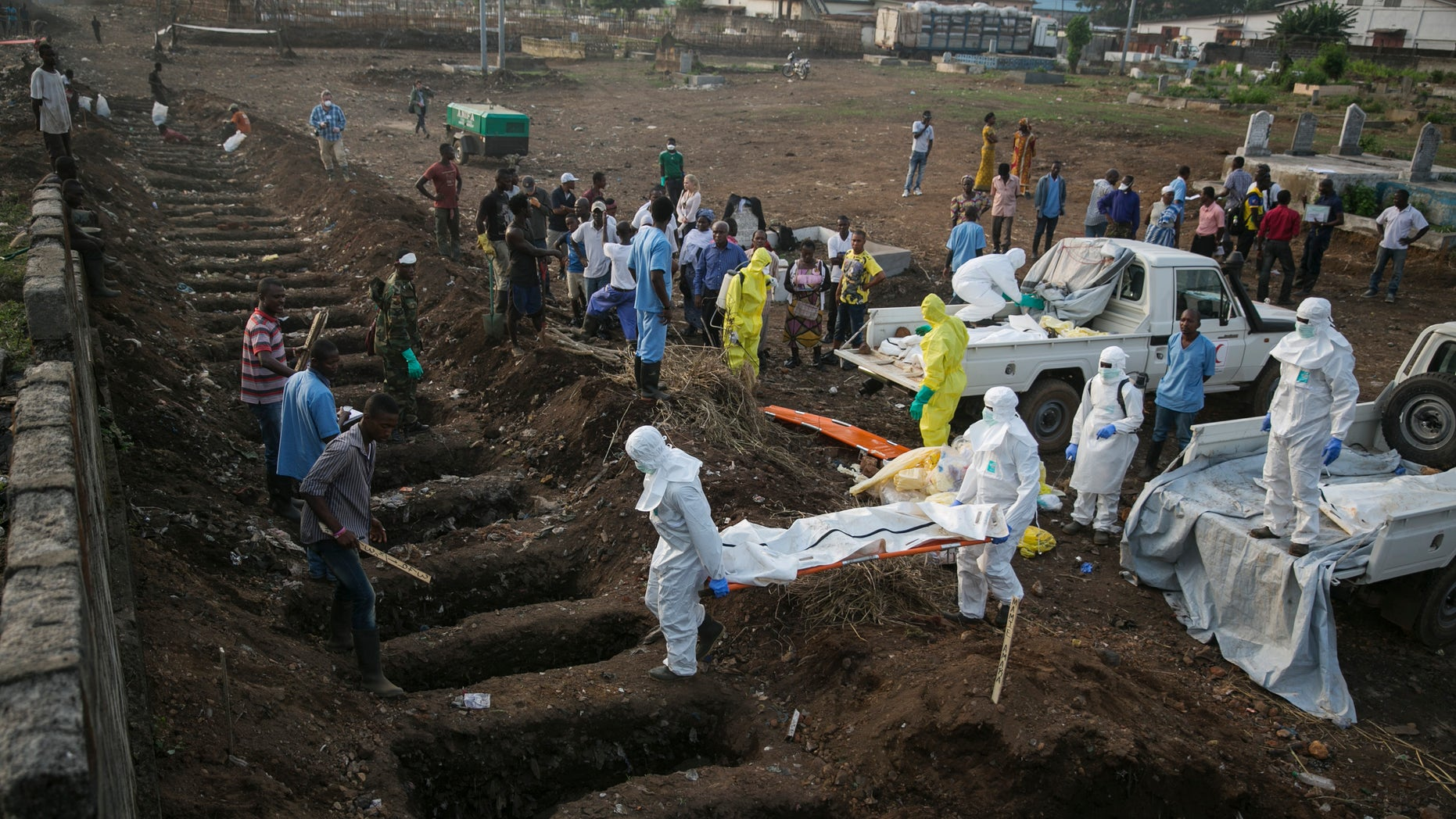 Health workers carry the body of an Ebola victim for burial at a cemetery in Freetown December 17, 2014.