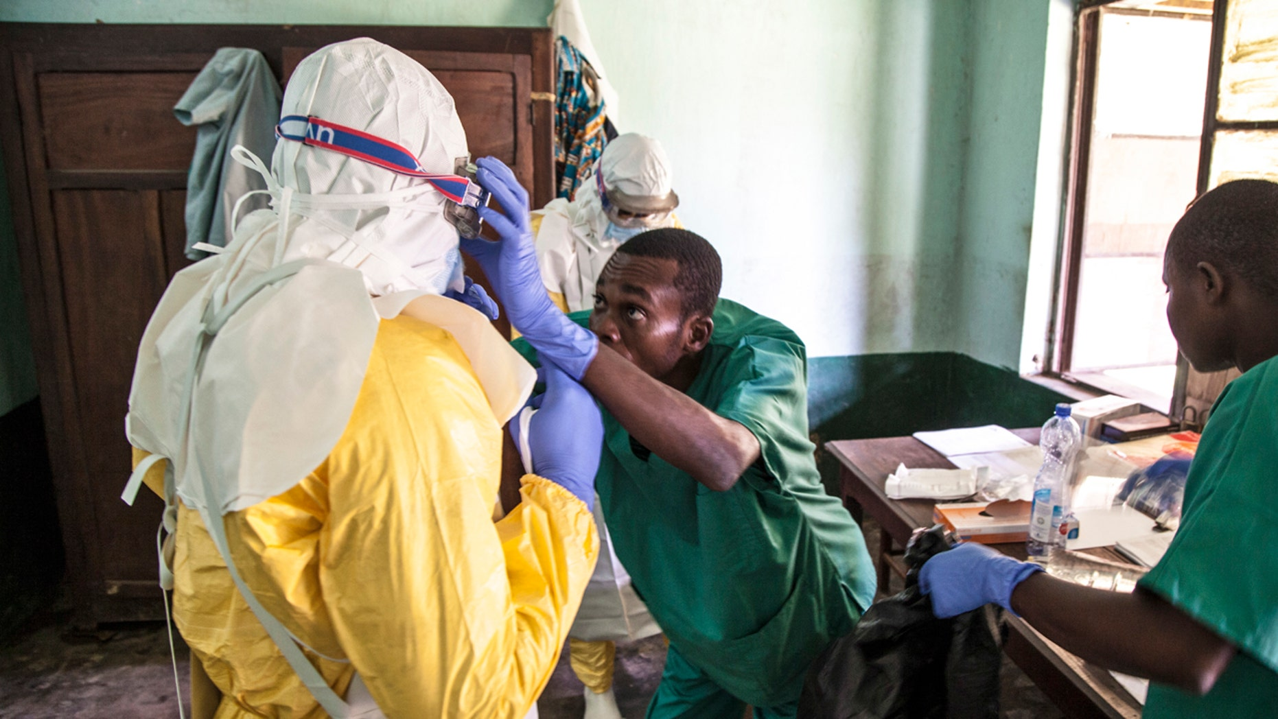 In this photo taken Saturday, May 12, 2018, health workers don protective clothing as they prepare to attend to patients in the isolation ward to diagnose and treat suspected Ebola patients, at Bikoro Hospital in Bikoro, the rural area where the Ebola outbreak was announced last week, in Congo.