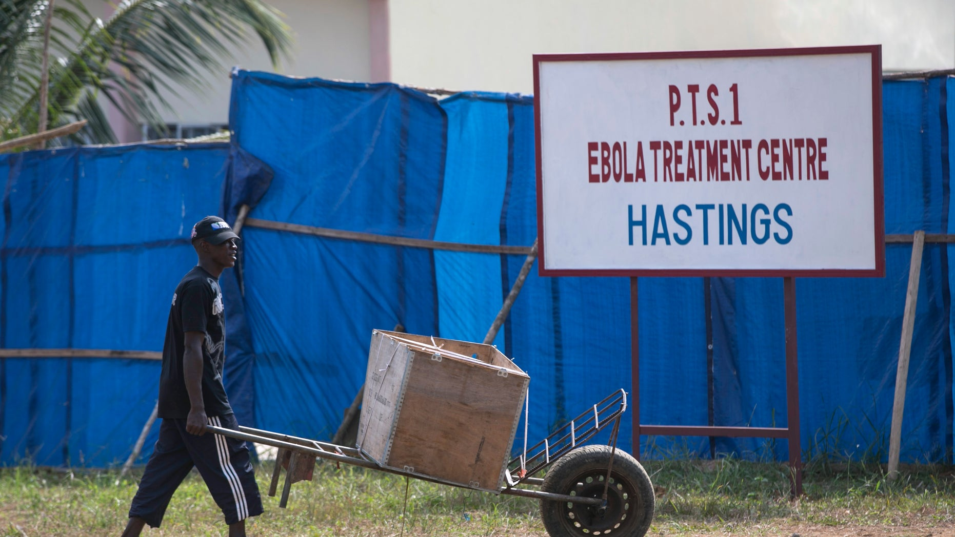 A man pushes a wheelbarrow past the entrance to Hastings Ebola treatment centre in a neighbourhood in Freetown December 21, 2014. REUTERS/Baz Ratner