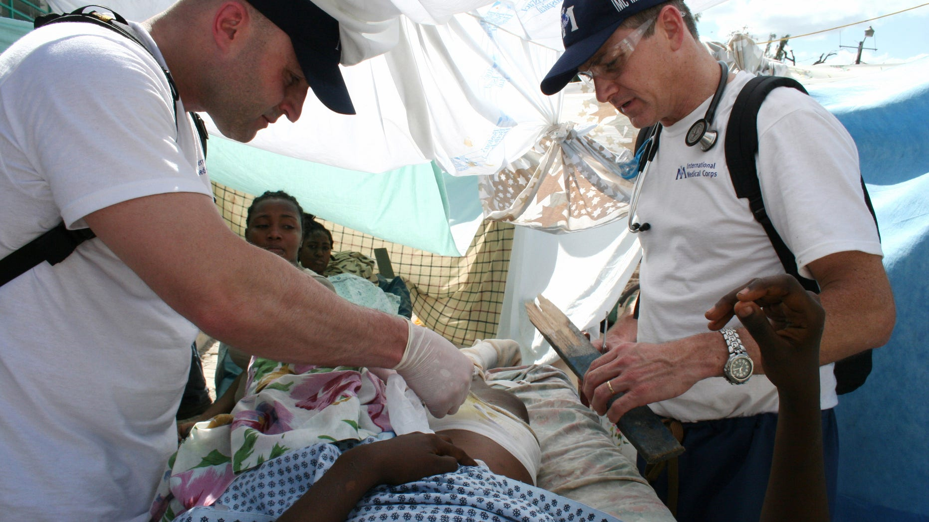 In this Jan. 16, 2010 photo provided by the International Medical Corps, Dr. Robert Fuller, right, joins Dr. Matthew Howell as they care for a person injured in the 2010 earthquake in Port-ua-Prince, Haiti.  AP Photo/International Medical Corps, Margaret Aguirre