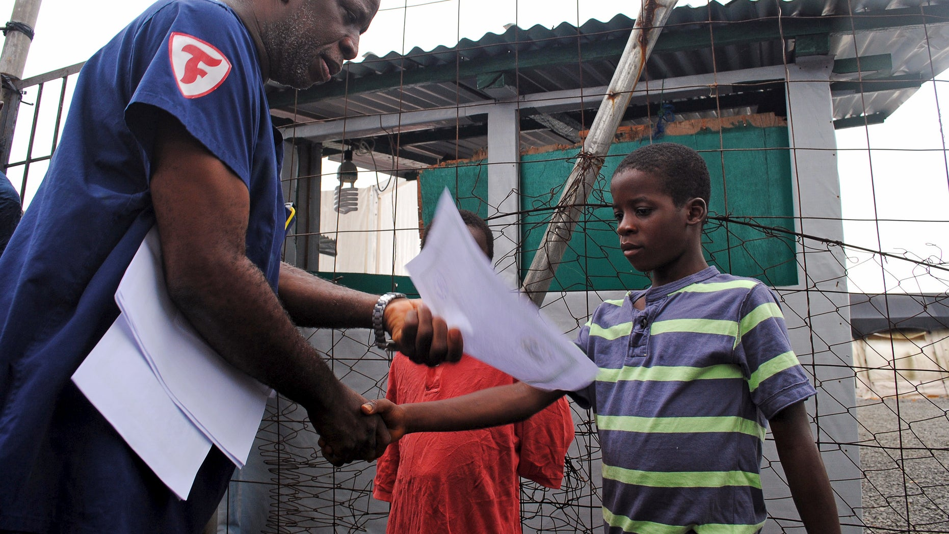 Moses Duo, 9, receives a certificate for being cured of the Ebola virus in Paynesville, Liberia, July 20, 2015. REUTERS/James Giahyue
