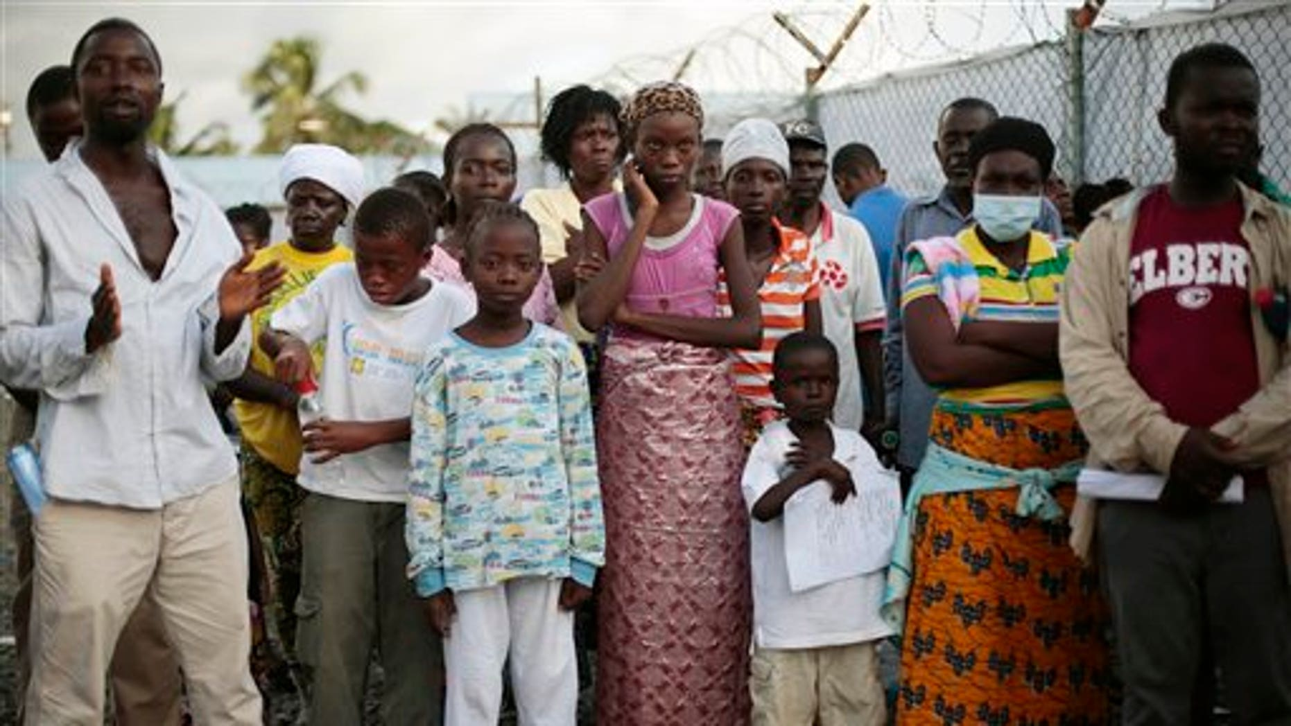 FILE - In this Tuesday, Sept. 30, 2014 file photo, patients being discharged from the Island Clinic Ebola treatment center in Monrovia, Liberia, wait to be sprayed with disinfectant. (AP Photo/Jerome Delay, File)