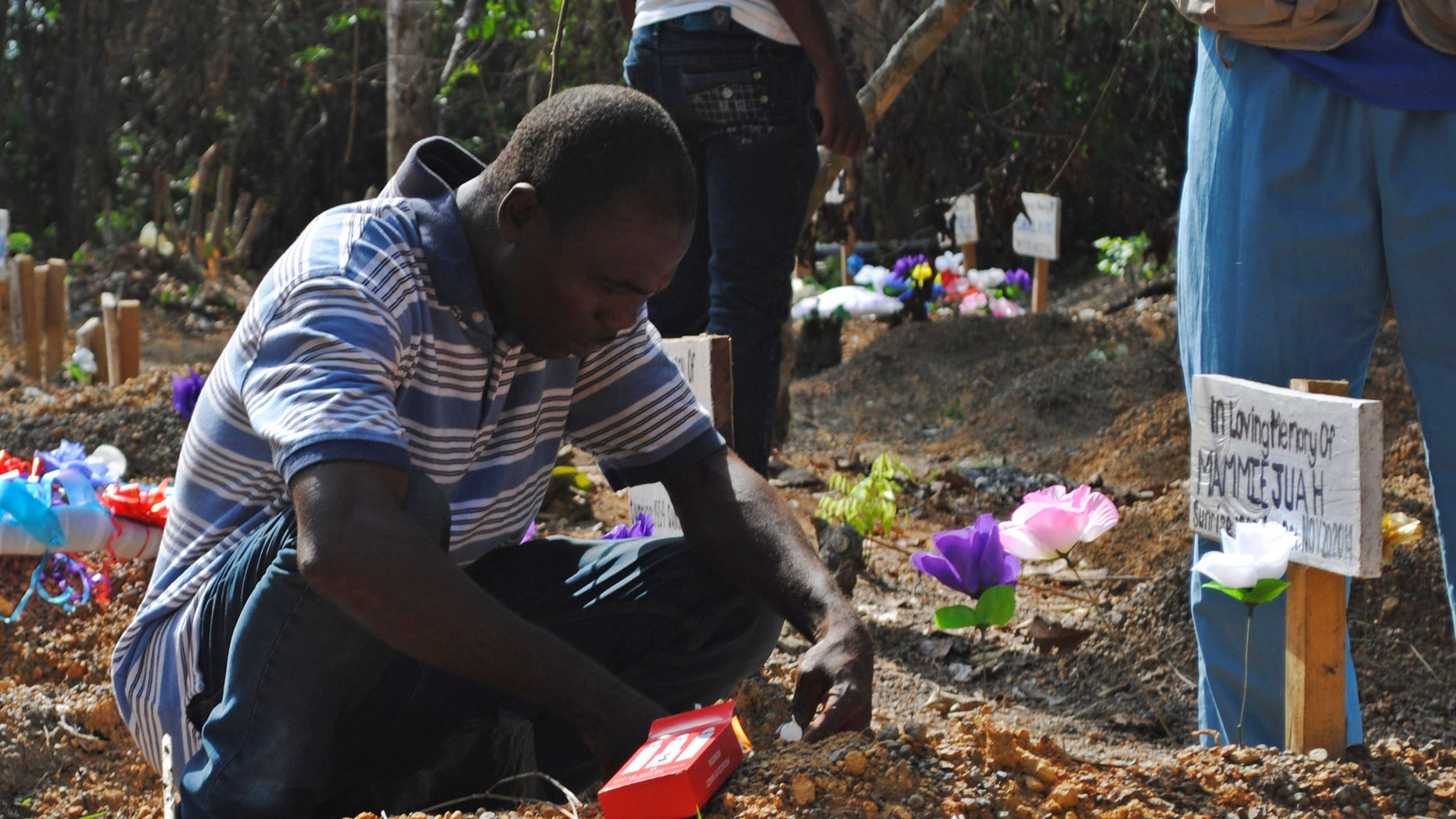 Survivor of Ebola virus Stanley Juah weeps at his son's grave at a cemetery for victims of Ebola virus in Suakoko, Liberia, March 11, 2015. Juah lost four of his family members and relatives to Ebola. REUTERS/James Giahyue