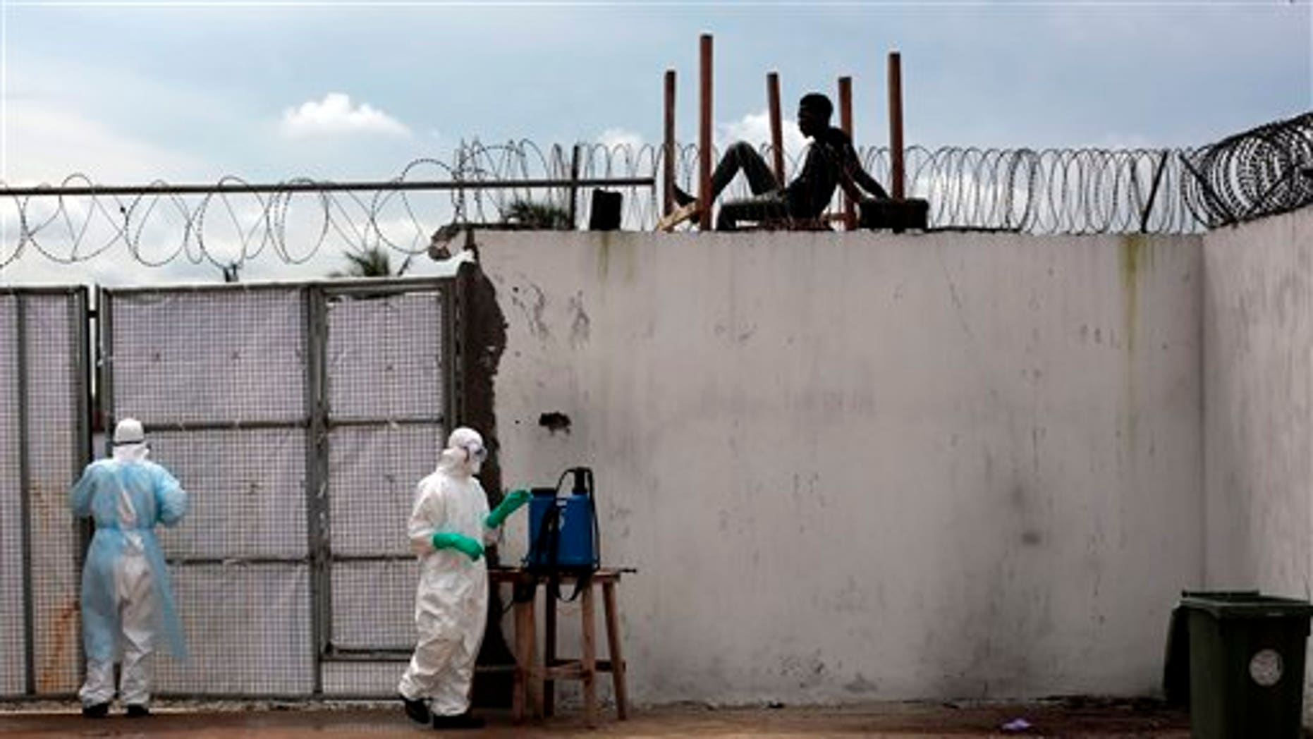 In this Friday, Sept. 26, 2014 file photo, health workers stand outside the Island Clinic Ebola isolation and treatment center in Monrovia, Liberia. (AP Photo/Jerome Delay, File)