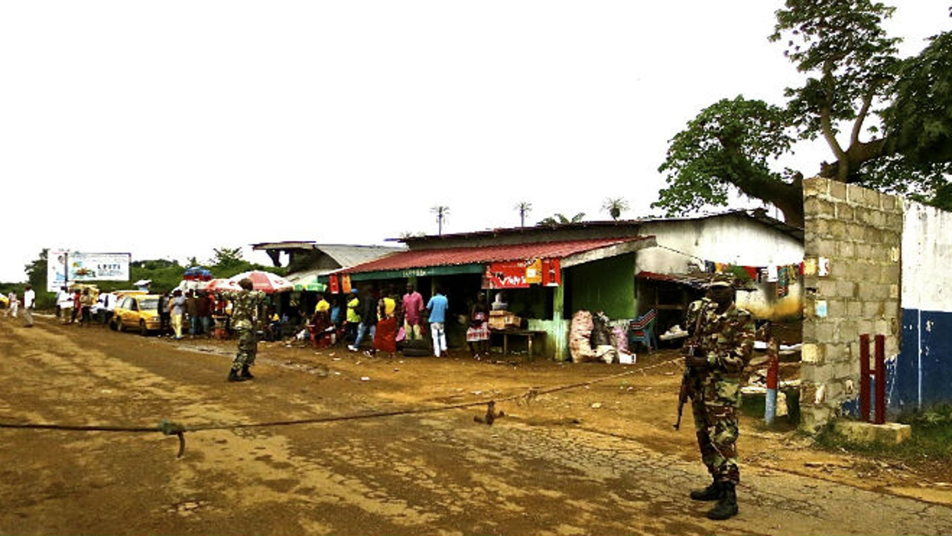 Soldiers from the Liberian army monitor a border checkpoint as part of Operation White Shield to control the Ebola outbreak, at an entrance to Bomi County in northwestern Liberia August 11, 2014. CREDIT: REUTERS/SABRINA KARIM