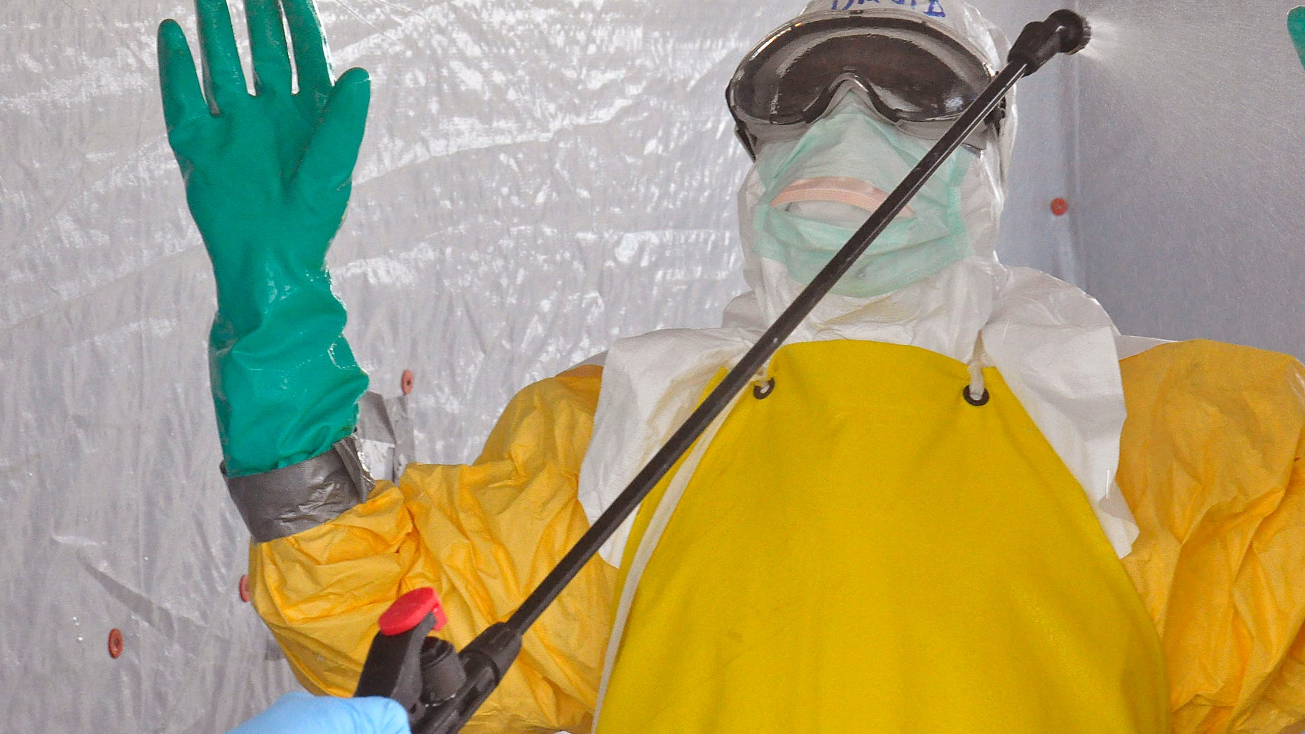 A health worker is sprayed with disinfectant after he worked with patients that contracted the Ebola virus, at a clinic  in Monrovia, Liberia, Monday, Sept. 8, 2014.  (AP Photo/Abbas Dulleh)