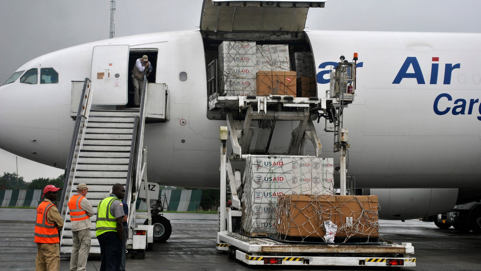 Workers are seen as the first consignment of U.S. Agency for International Development (USAID) medical equipment towards the fight against Ebola is offloaded at the Roberts International Airport in Monrovia, August 24, 2014. REUTERS/James Giahyue