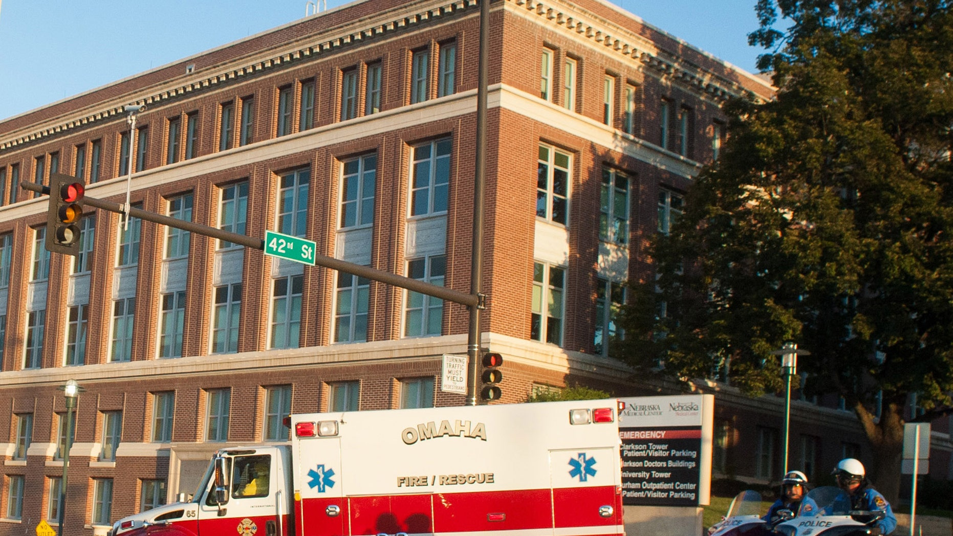 An ambulance transports Ashoka Mukpo, who contracted Ebola while working in Liberia, to the Nebraska Medical Center's specialized isolation unit Monday, Oct. 6, 2014, in Omaha, Neb., where he will be treated for the deadly disease. (AP Photo/Dave Weaver)