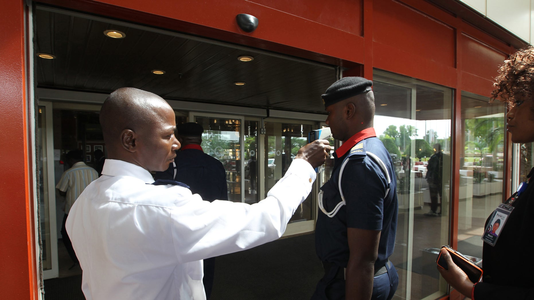 A security personnel screens a man's temperature at the entrance of Transcorp Hilton hotel in Abuja September 3, 2014. REUTERS/Afolabi Sotunde